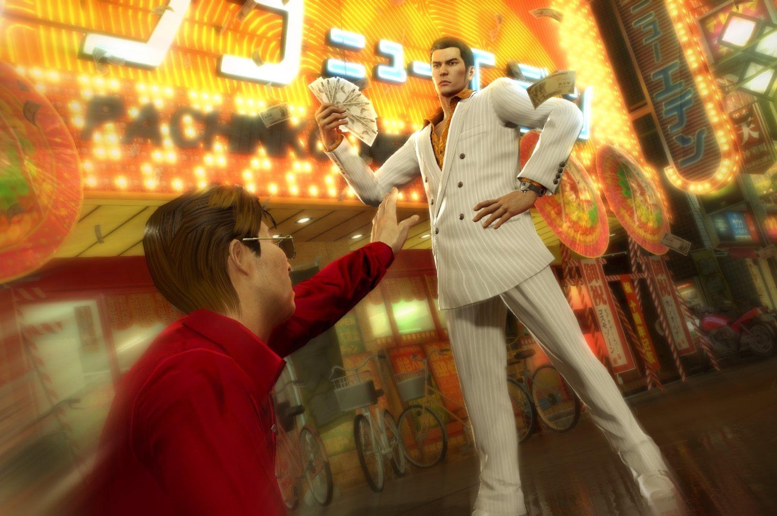 A screengrab from the game shows Kiryu Kazuma with a wad of cash in Yakuza 0. (Credit: Sega Games)
