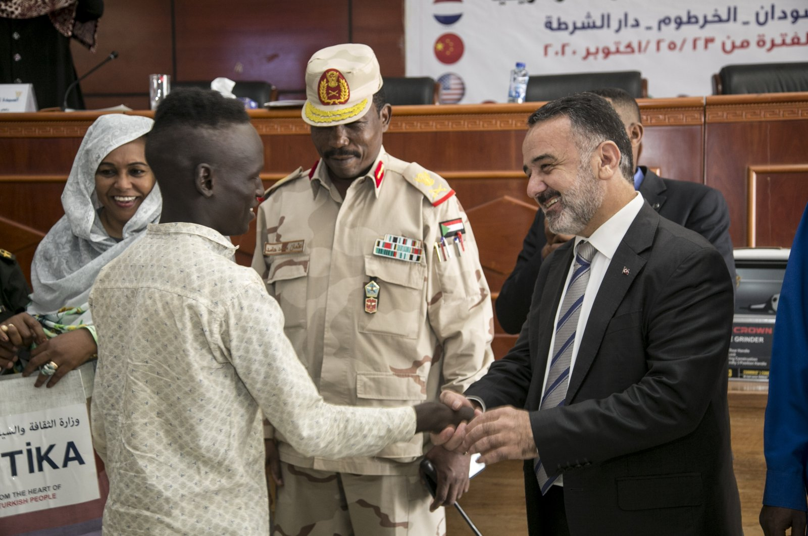 Ahmed Ali (L), one of the youth who benefited from the aid, shakes hands with Turkish Ambassador İrfan Neziroğlu (R), in Khartoum, Sudan, Oct. 25, 2020. (AA Photo)