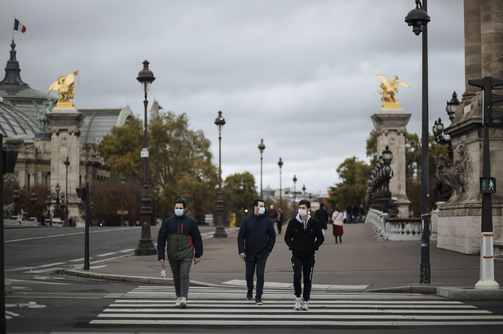 People wearing masks walk in the Invalides district of Paris, Oct. 25, 2020. (AP Photo)