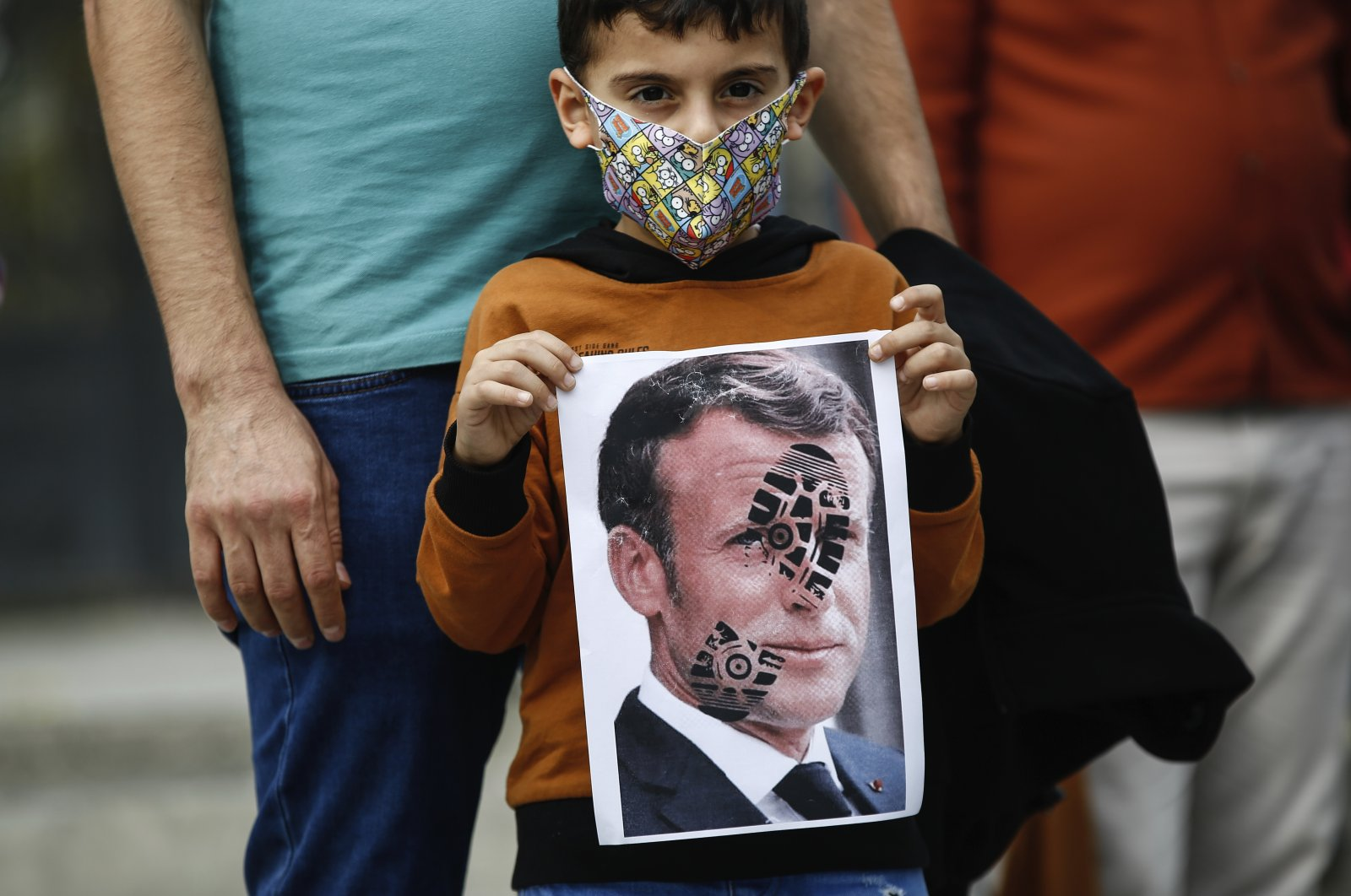 A child holds a photograph of France's President Emmanuel Macron, stamped with a shoe mark, during a protest against France in Istanbul, Oct. 25, 2020. (AP)