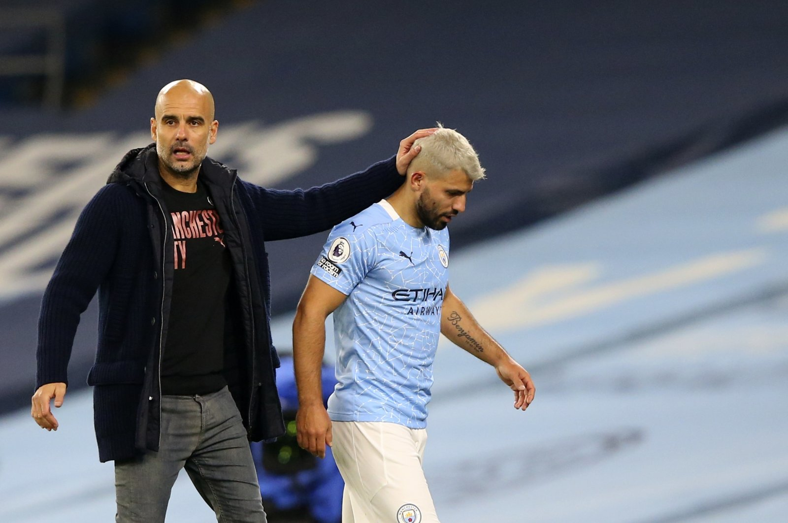 Manchester City coach Pep Guardiola (L) consoles Sergio Aguero after being substituted during a Premier League match against Arsenal, in Manchester, England, Oct. 17, 2020. (AP Photo)