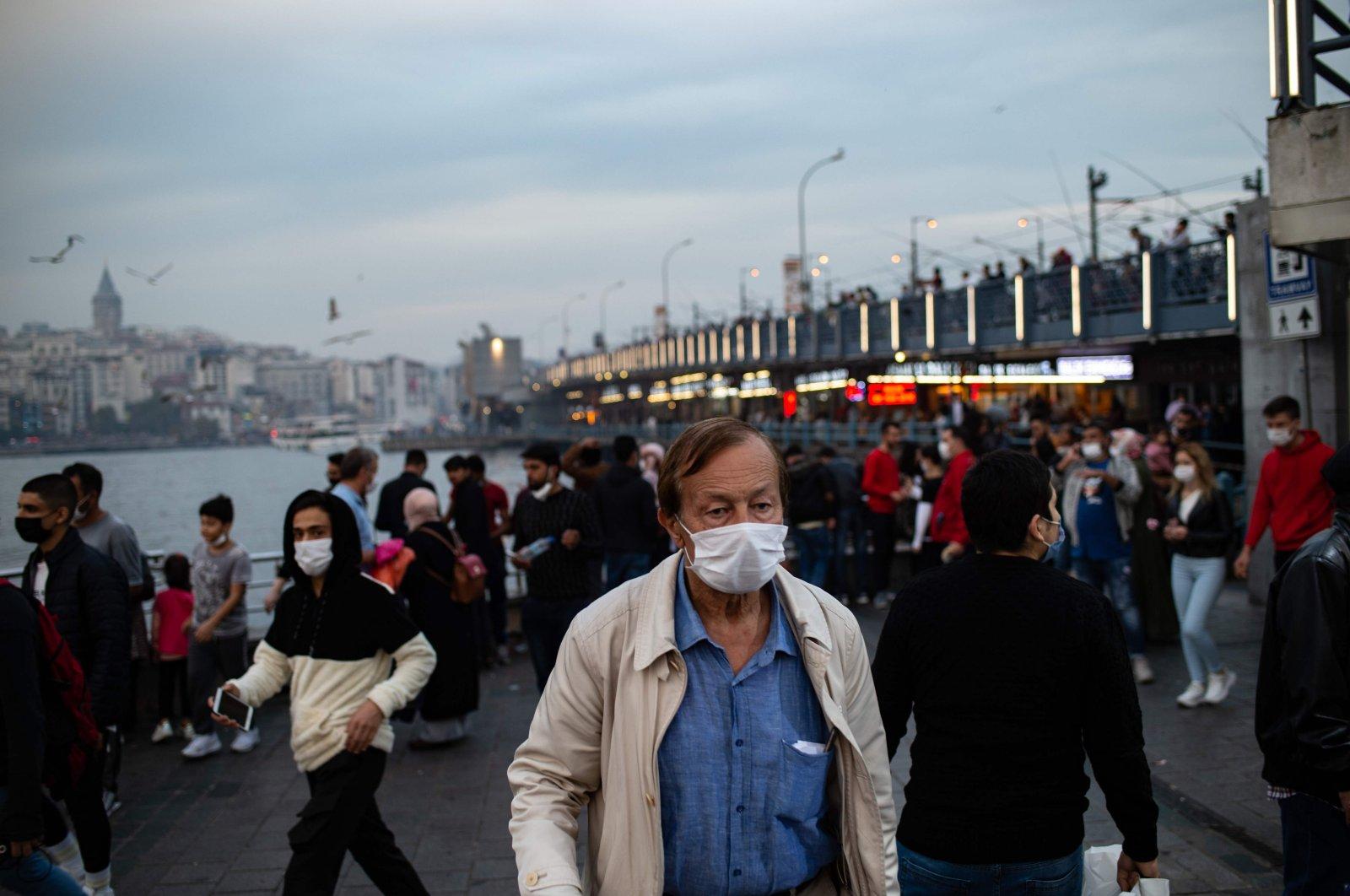 A man, wearing a face mask, walks near the Galata bridge, in Istanbul, Turkey, Oct. 25, 2020. (AFP Photo)