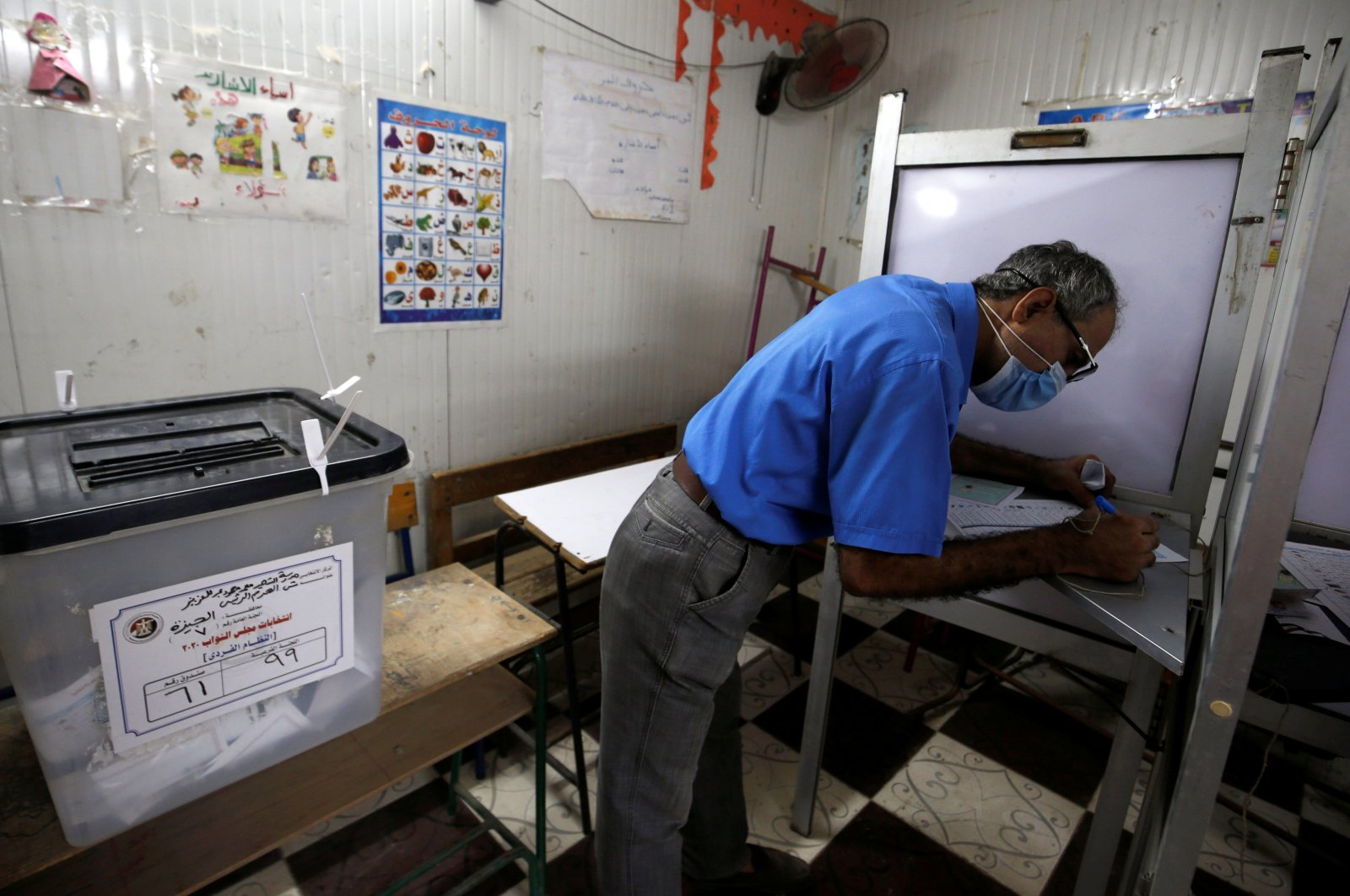 A man wearing a protective mask casts his ballot at a school used as a polling station, Giza, Oct. 25, 2020. (REUTERS Photo)