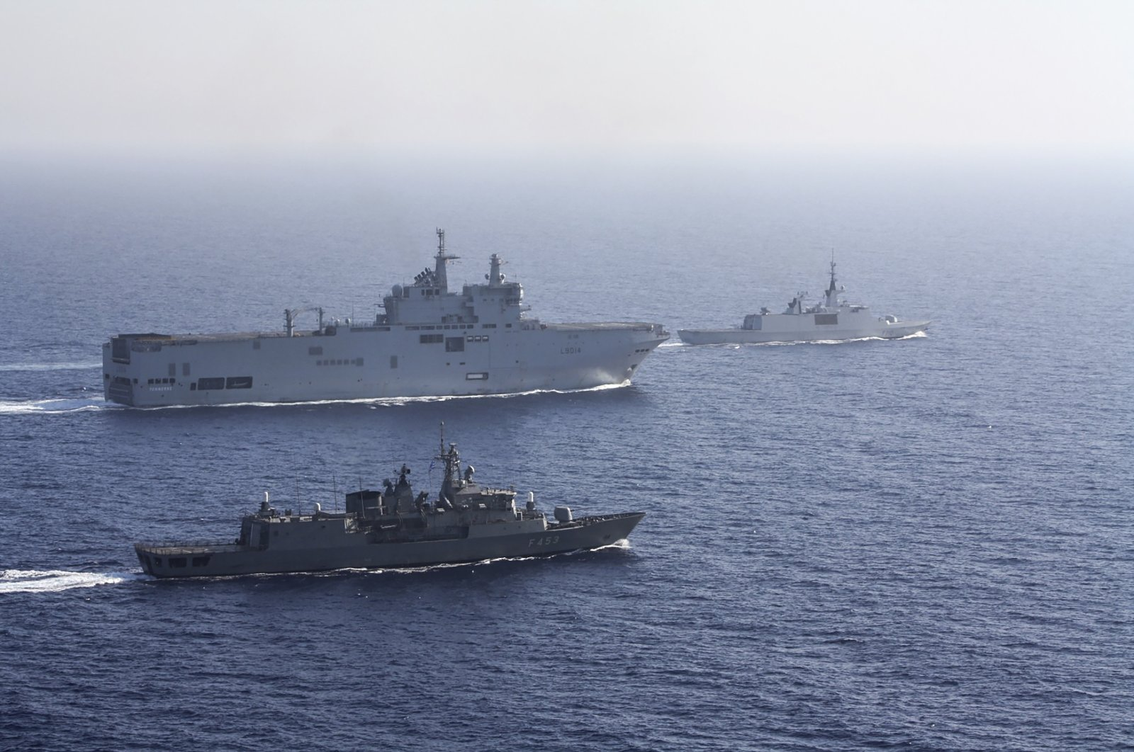 In this photo provided by the Greek National Defence Ministry, a French Tonnerre helicopter carrier, rear left, is escorted by Greek and French military vessels during a maritime exercise in the Eastern Mediterranean, Aug. 13, 2020. (AP Photo)