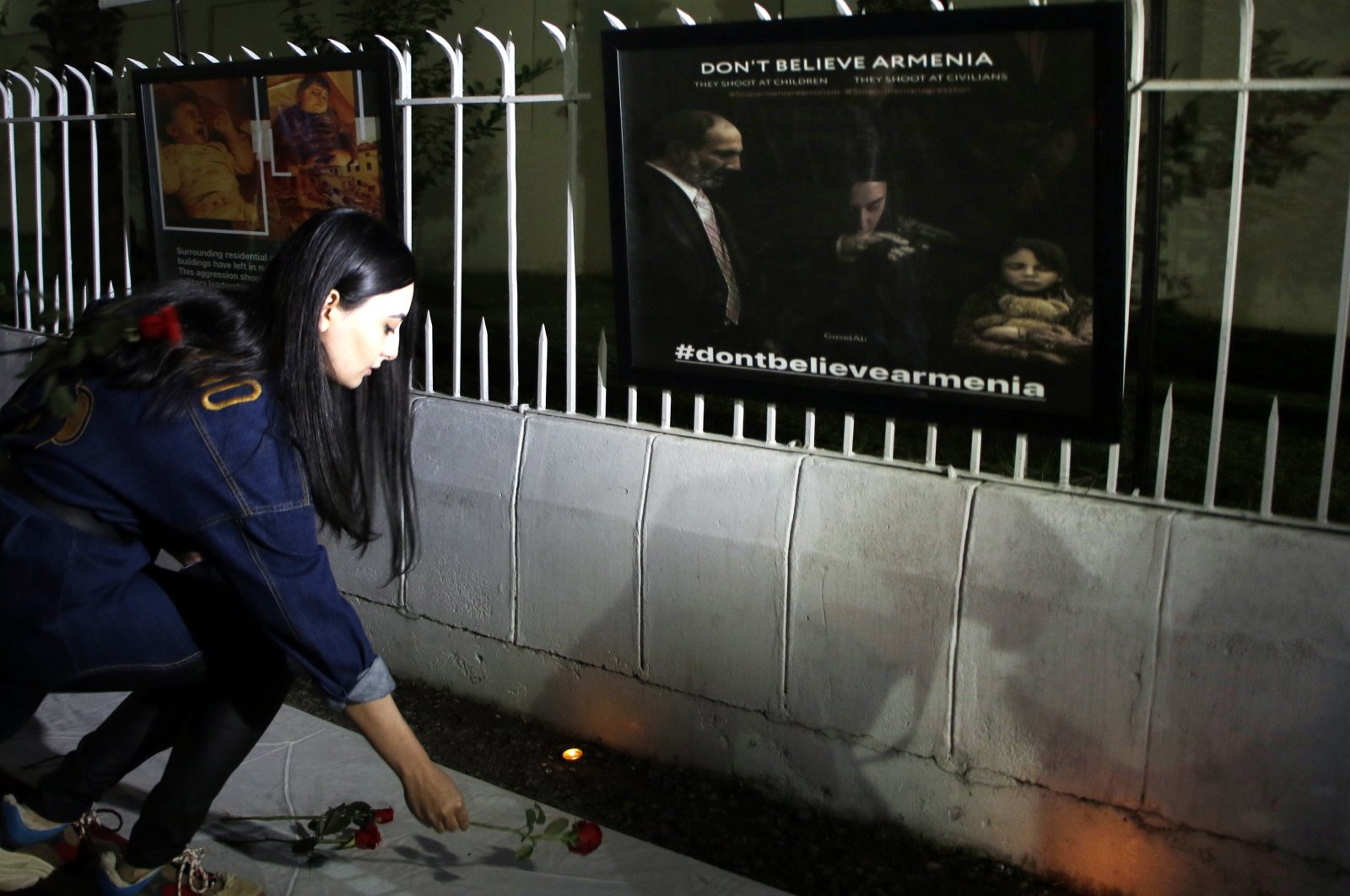 A person lays flowers as diplomats and staff of different foreign embassies gather outside the embassy of Azerbaijan during a memorial for the children killed by Armenian separatists, in Islamabad, Pakistan, Oct. 26, 2020. (EPA Photo)