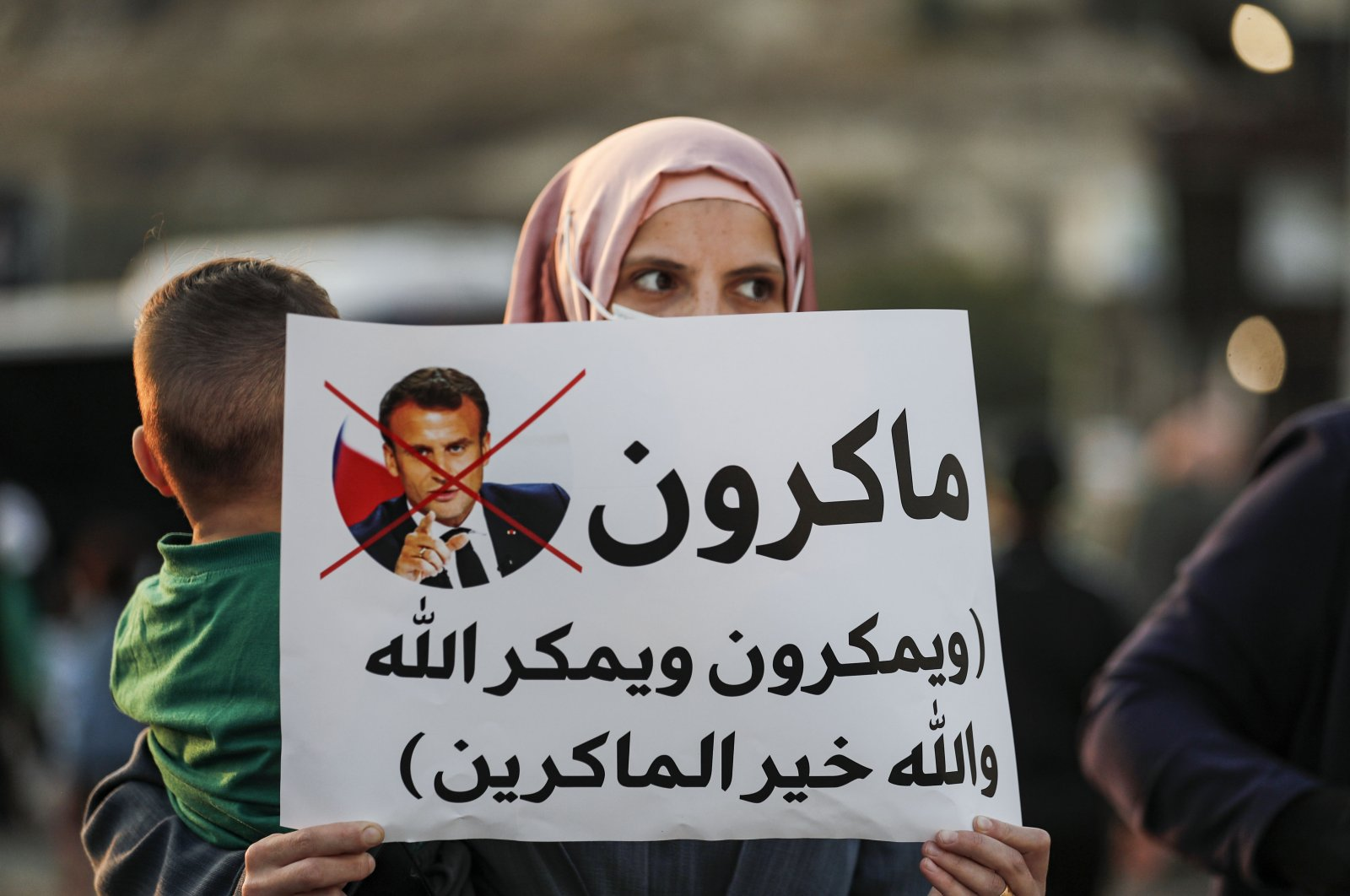An Arab-Israeli, Muslim demonstrator, holding a child and clad in a mask due to the COVID-19 pandemic, holds up a sign during a rally protesting against French President Emmanuel Macron's anti-Islam remarks, in the Arab town of Umm-Al Fahm, Haifa district, northern Israel, Oct. 25, 2020. (AFP Photo)