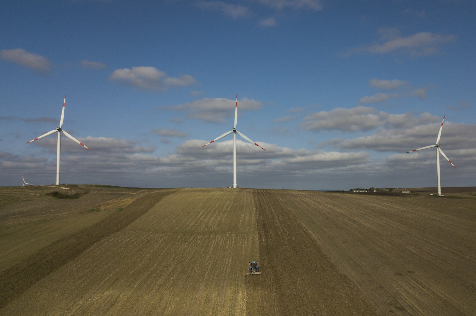 An aerial picture taken with a drone shows a Turkish farmer plowing his farmland with a tractor in front of wind turbines in the countryside of Istanbul, Turkey, Oct. 22, 2020.  (EPA Photo)