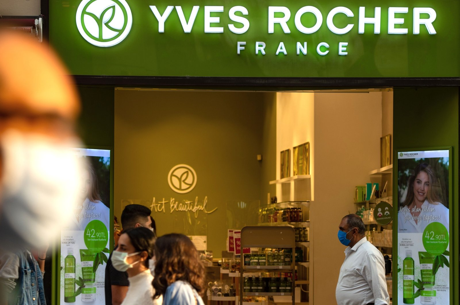 """Tourists wait in front of the French brand shop """"Yves Rocher"""" in Istanbul, Oct. 26, 2020. (AFP Photo)"""