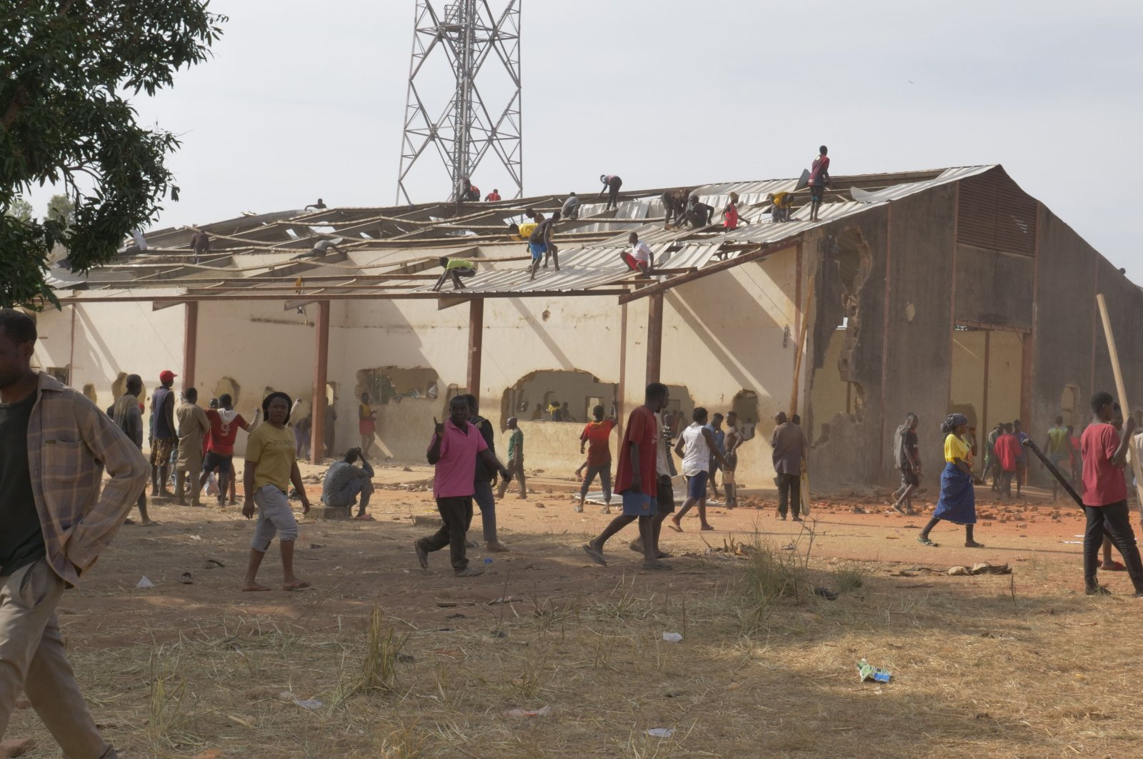 People take the metal sheets off the roof of a warehouse during a mass looting of a warehouse containing COVID-19 food palliatives that were not distributed to relieve people's hunger during the lockdown, Jos, Nigeria, Oct. 24, 2020. (AFP Photo)