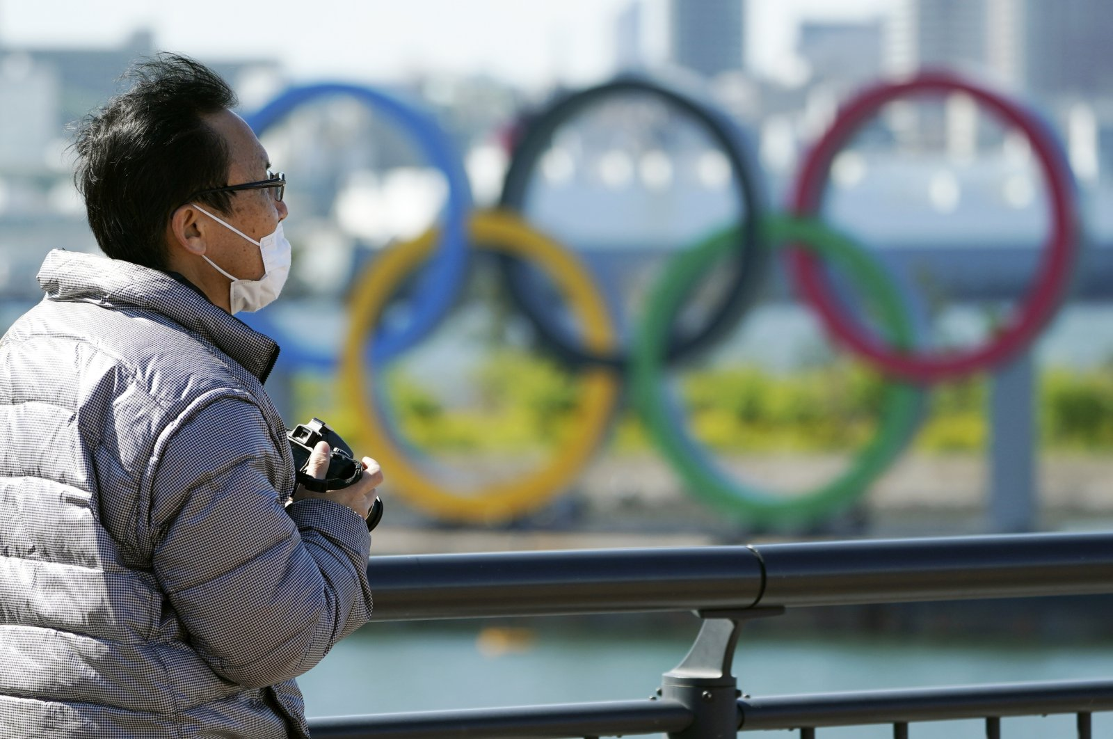 A visitor wearing a mask stands near the Olympic rings, in Tokyo, Japan, March 24, 2020. (AP Photo)