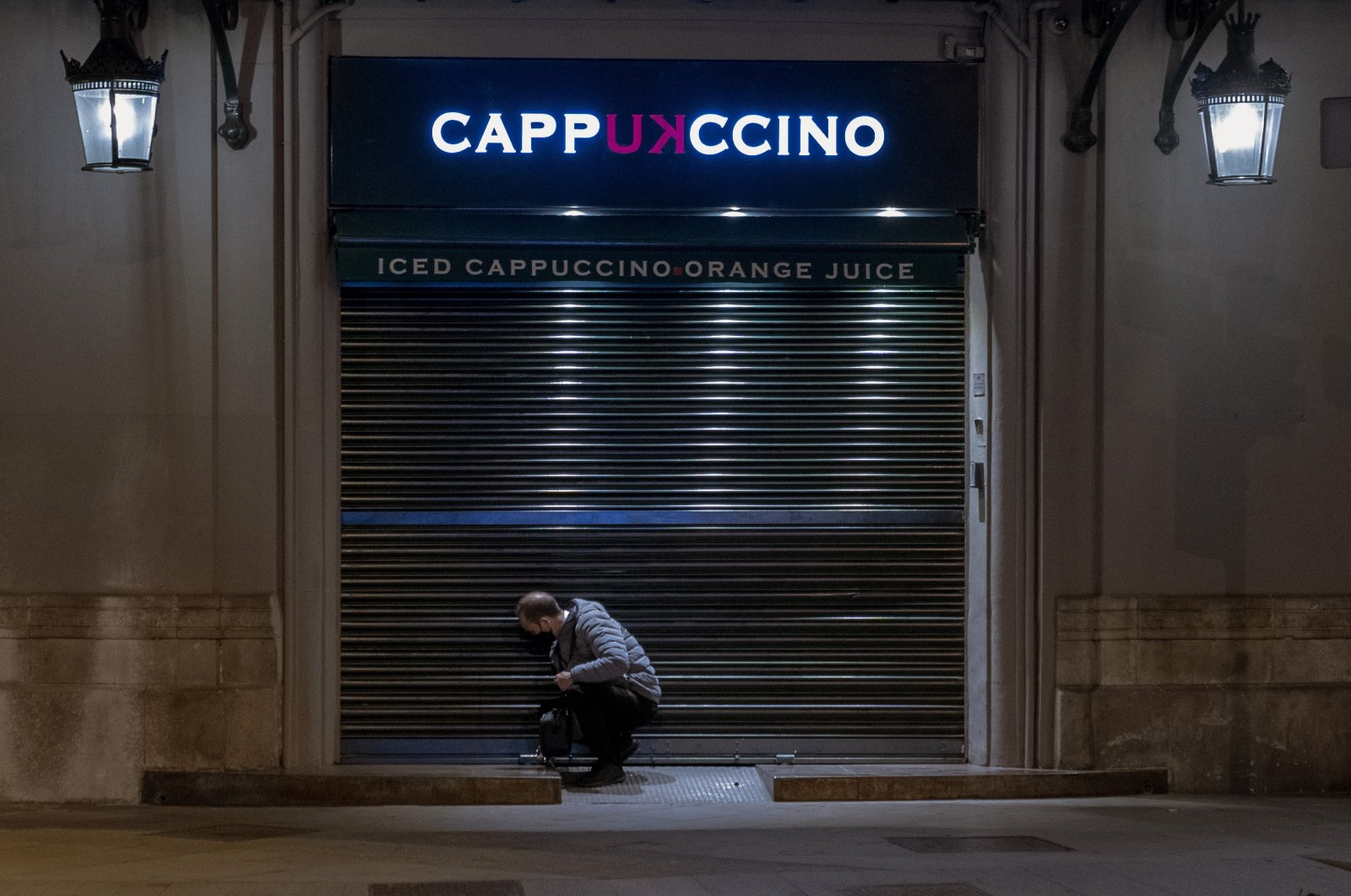 An employee closes his cafeteria before curfew in Barcelona, Spain, Oct. 26, 2020. (AP Photo)