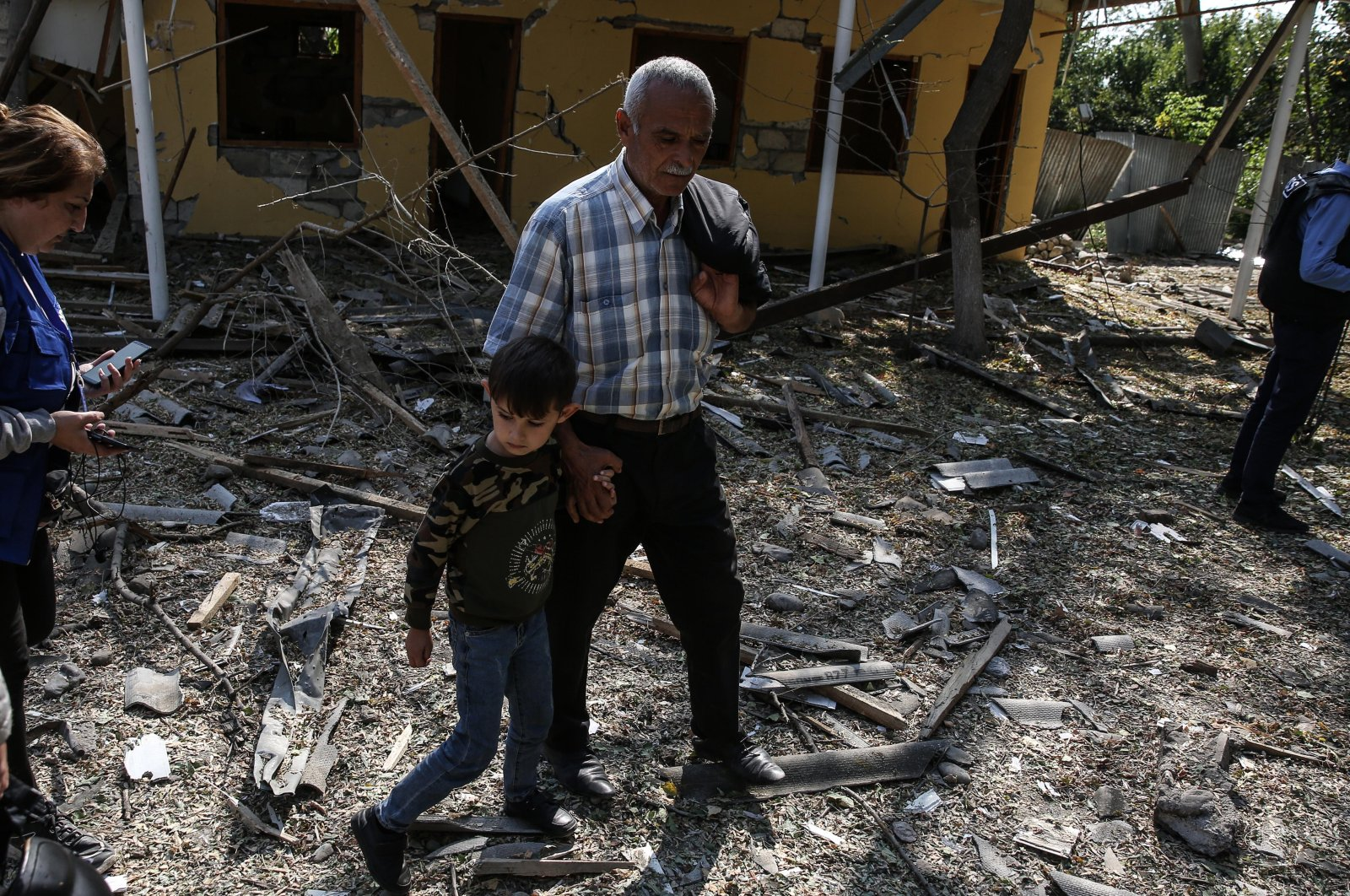 A man and a child walk in front of a home destroyed in Armenian shelling in the Azerbaijani city of Barda on Oct. 12, 2020. (AA File Photo)