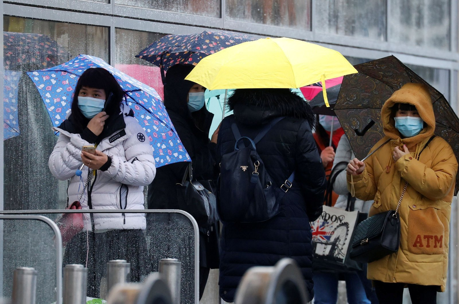 People wearing face masks shelter under umbrellas outside a department store, Manchester, Britain, Oct. 26, 2020. (REUTERS Photo)