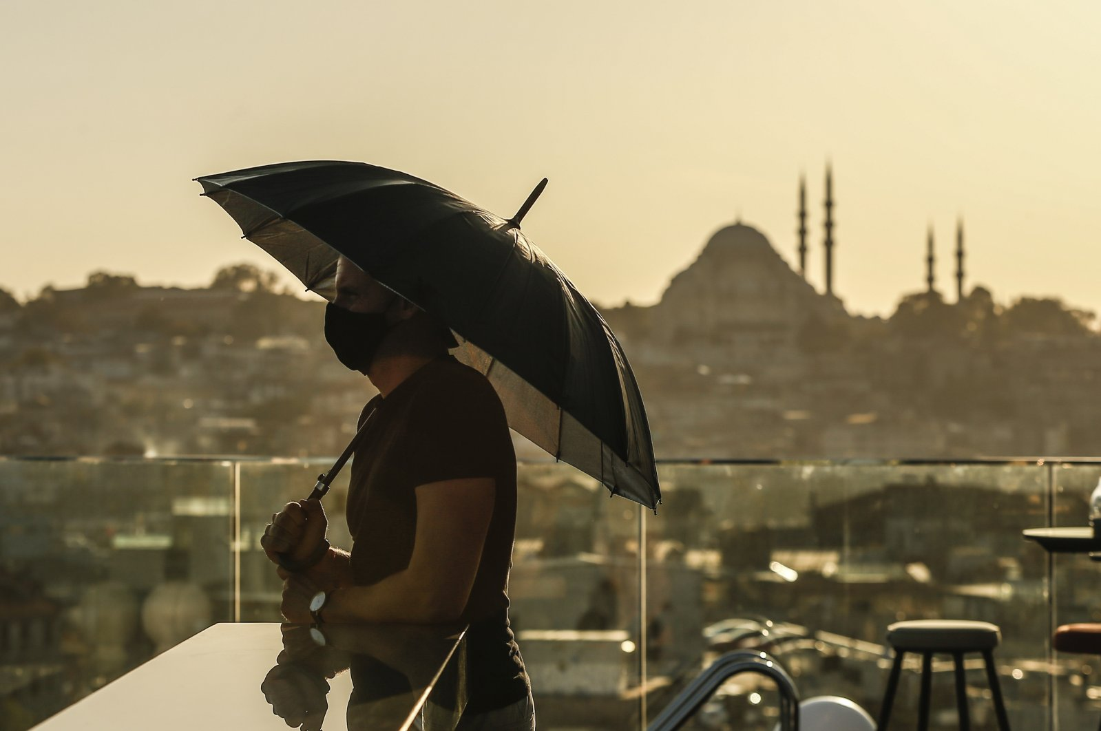 A tourist, wearing a protective mask to help prevent the spread of the coronavirus, enjoys the view backdropped by the Süleymaniye Mosque in Istanbul, Oct. 21, 2020. (AP Photo)