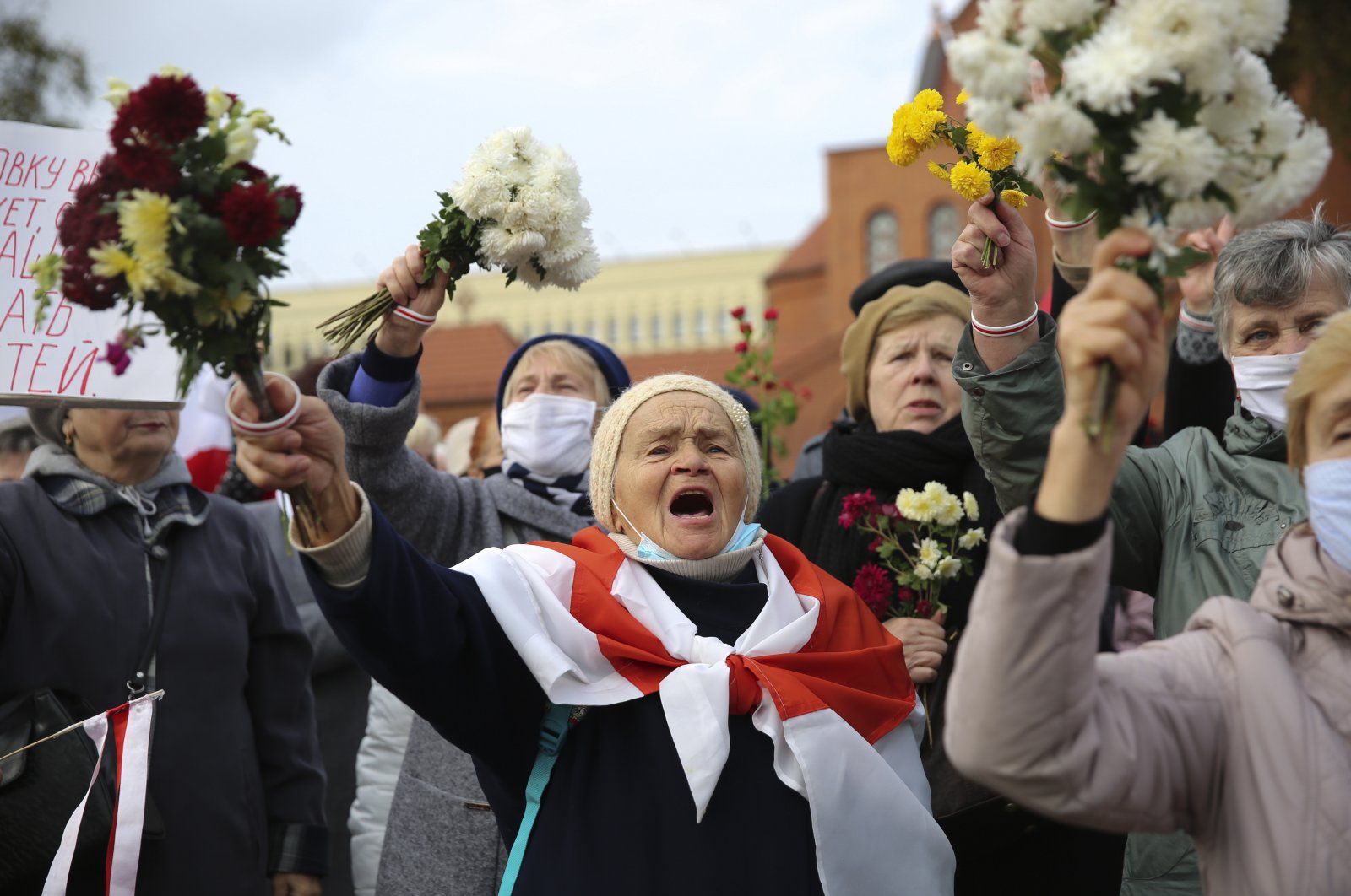 People, most of them pensioners, wave bunches of flowers during an opposition rally to protest the official presidential election results in Minsk, Belarus, Oct. 26, 2020. (AP Photo)