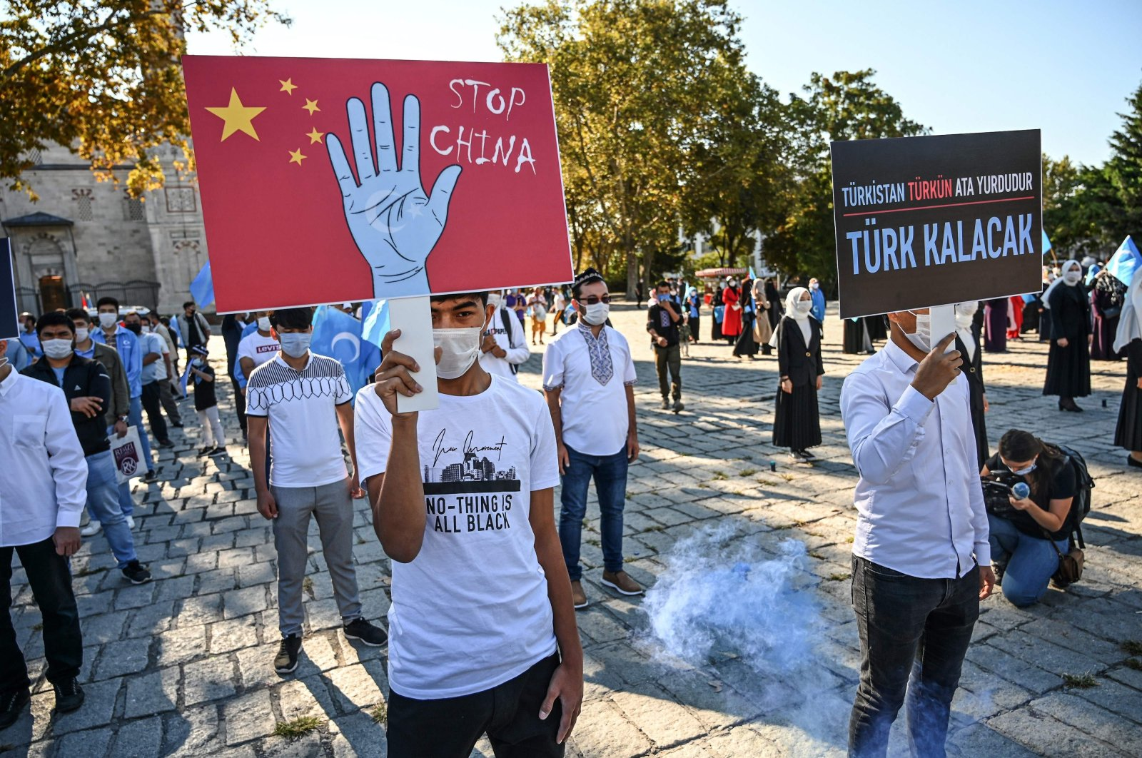 "A man holds a placard reading ""Stop China"" during a demonstration against China's treatment of Muslim minorities in Xinjiang region, at Beyazid Square in Istanbul, Oct. 1, 2020. (AFP Photo)"