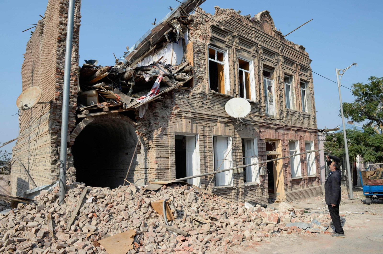 Local man looks at a residential building damaged by shelling during the ongoing military conflict between Armenia and Azerbaijan over the occupied region of Nagorno-Karabakh, in the city of Ganja, Azerbaijan, on Oct. 27, 2020. (AFP)