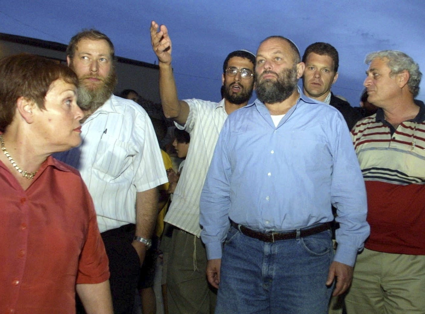 In this Oct. 13, 2002 file photo, Israel's then-Infrastructure Minister Effie Eitam (C) listens to Jewish settlers when visiting Mitzpeh Assaf, an illegal outpost which Israel's Defense Minister said will be dismantled, near the settlement of Ofra, north of Jerusalem. (AP Photo)