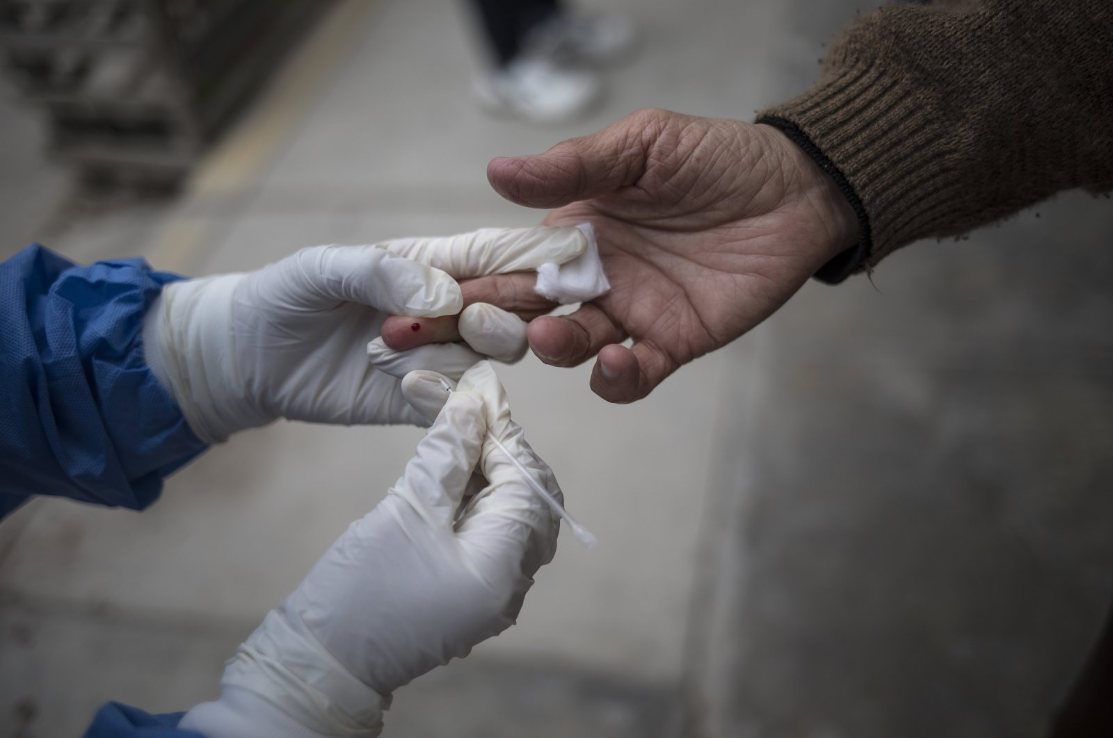 A healthcare worker takes a blood sample during a house-to-house rapid antibody test drive in Villa el Salvador, on the outskirts of Lima, Peru, June 30, 2020. (AP Photo)