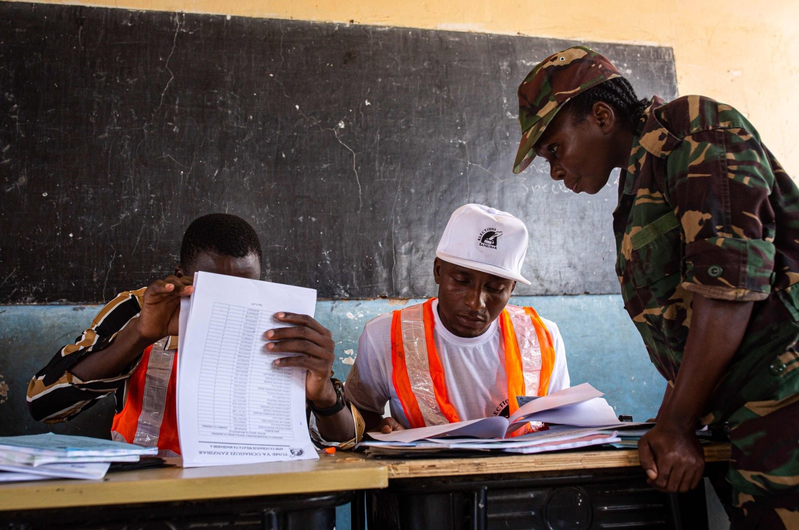 Zanzibar Electoral Commission (ZEC) officials check a security forces officer's ID at Mtupepo Primary School in Daraja Bovu, Zanzibar, Oct. 27, 2020. (AFP Photo)