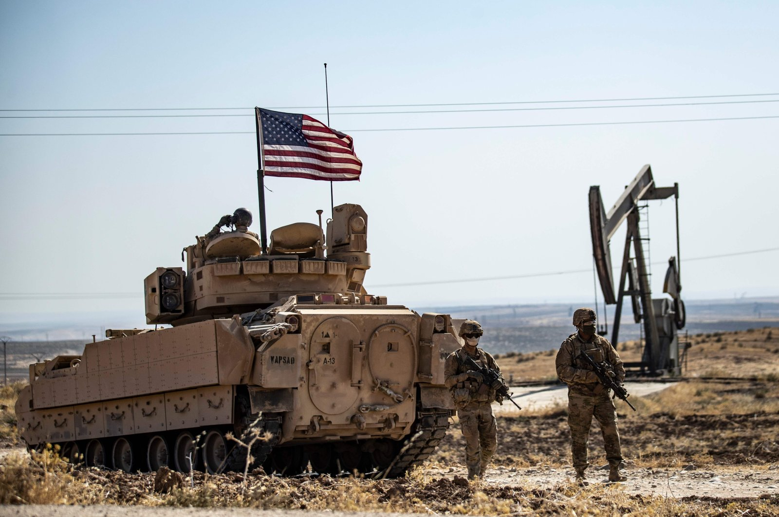U.S. soldiers walk near a Bradley Fighting Vehicle (BFV) during a military patrol in northeastern Syria, Oct. 27, 2020. (AFP Photo)