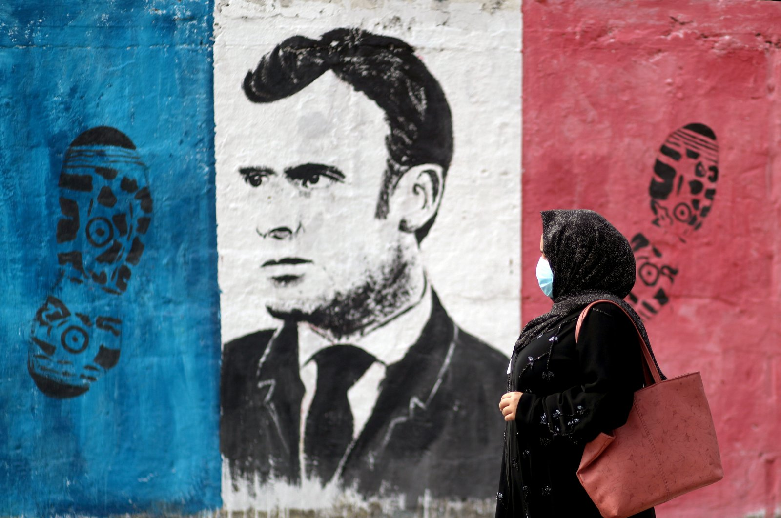 A Palestinian woman walks past an anti-French President Emmanuel Macron mural painted by an artist to protest against the publication of a cartoon of the Prophet Muhammad in France and Macron's comments, in Gaza City, Oct. 28, 2020. (Reuters Photo)