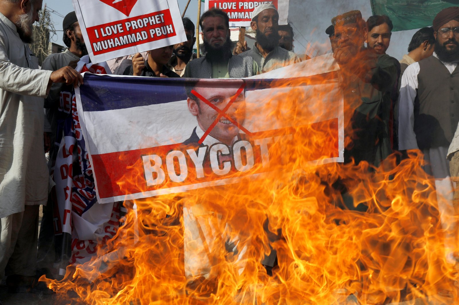 People chant slogans as they set fire to a banner with a crossed-out image of French President Emmanuel Macron during a protest against cartoon publications of the Prophet Mohammad in France and Macron's comments, in Karachi, Pakistan, Oct. 27, 2020. (REUTERS Photo)