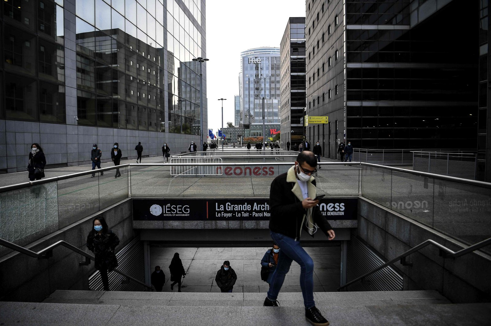 People wearing protective face masks walk by high-rise buildings, Paris, France, Oct. 16, 2020. (AFP Photo)