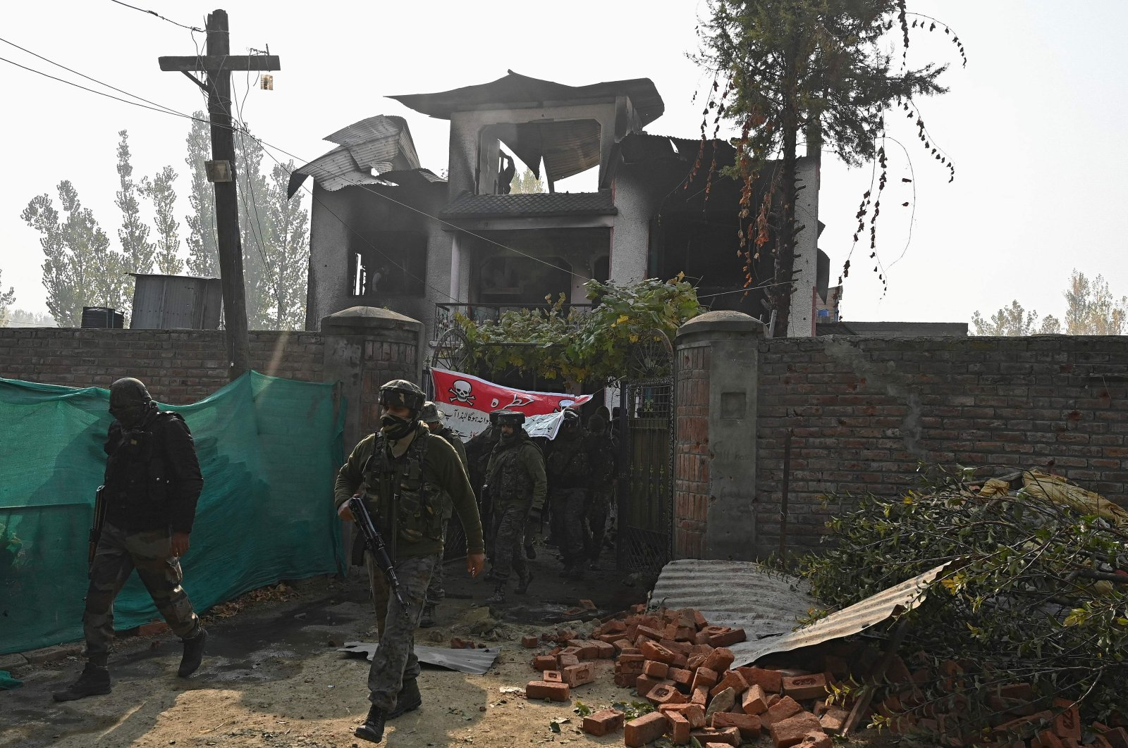 Indian security personnel walk outside a damaged house in the Budgam district on the outskirts of Srinagar, Jammu and Kashmir, Oct. 28, 2020. (AFP Photo)
