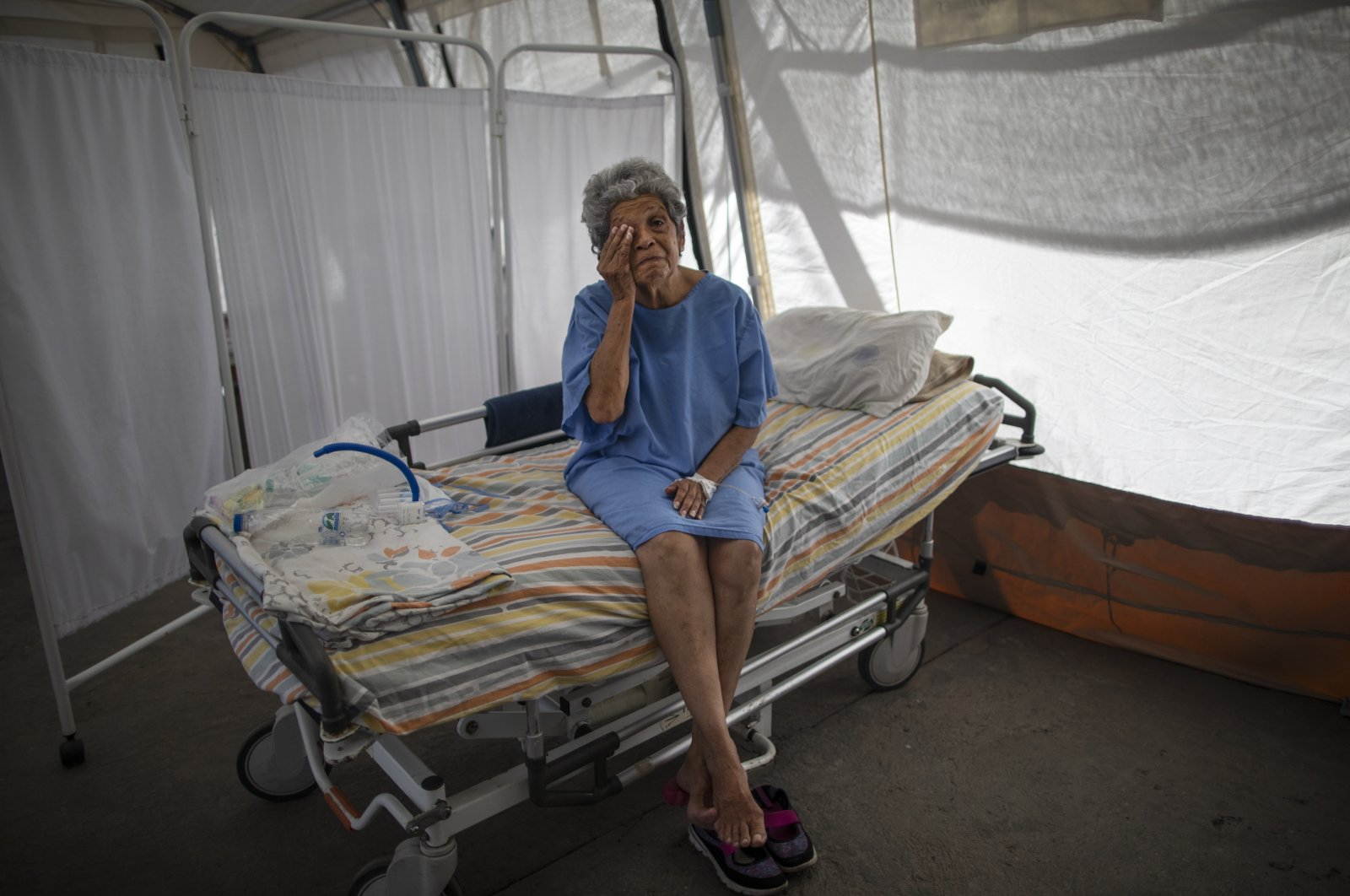 A 76-year-old patient wipes tears as she explains her battle with COVID-19 under a tent for patients who will be discharged from the Perez de Leon II Hospital in Caracas, Venezuela, Sept. 22, 2020. (AP Photo)