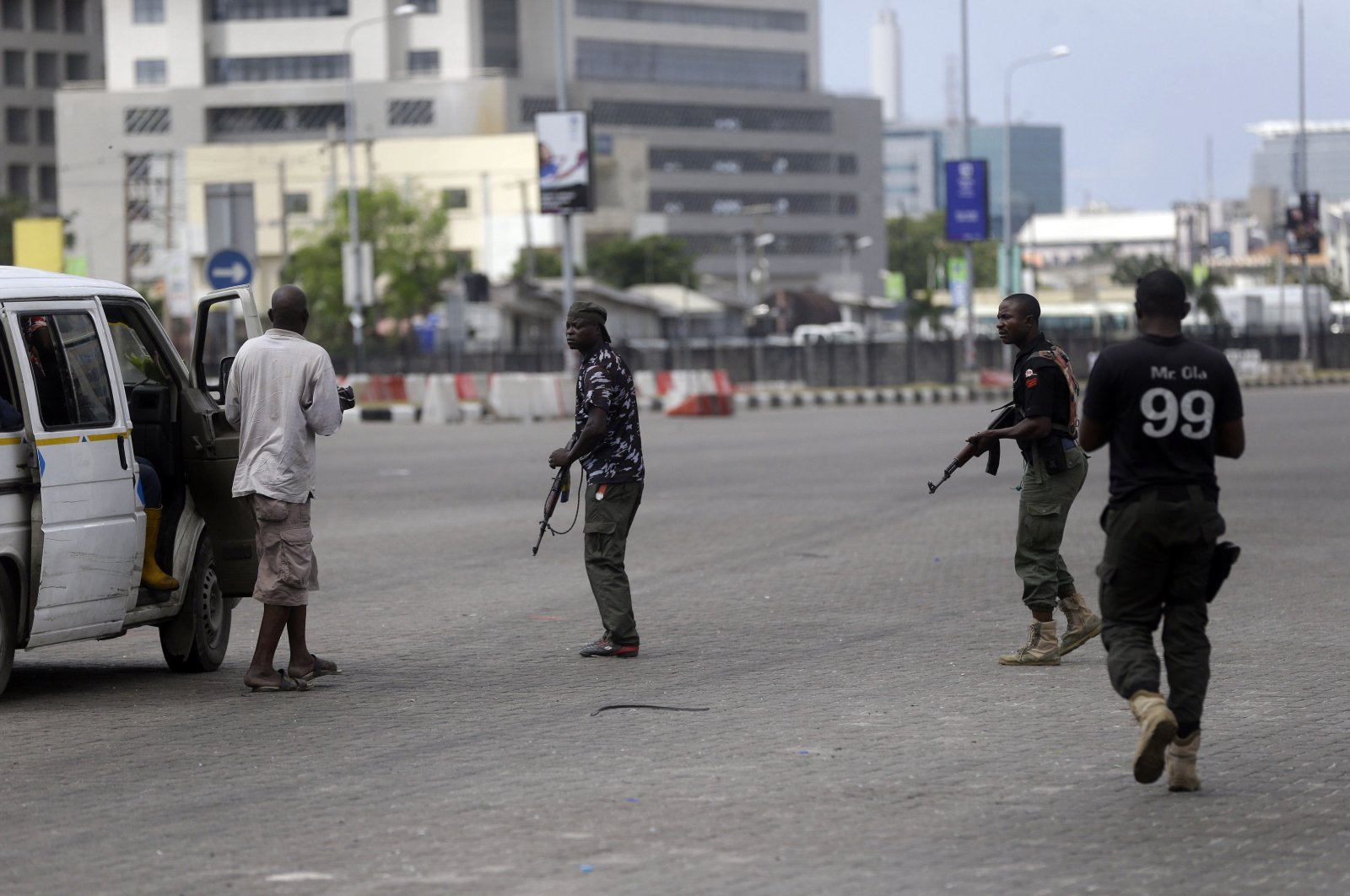 Police officers stop and search a bus carrying passengers around the Lekki toll gate in Lagos, Nigeria, Oct. 23, 2020. (AP Photo)