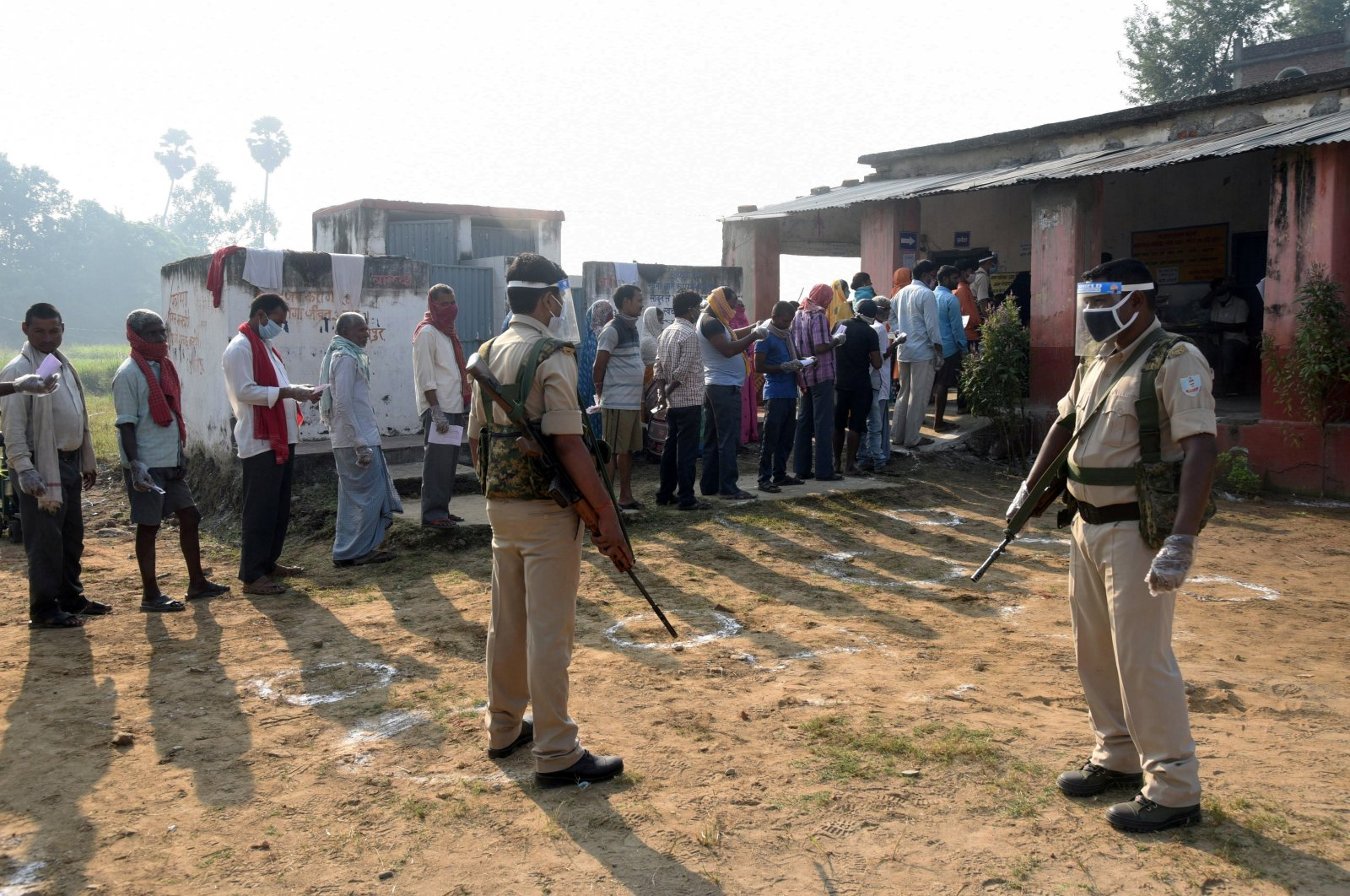 Policemen wearing protective face shields stand guard as voters stand in a queue to cast their vote outside a polling booth at a village on the outskirts of Patna in the eastern state of Bihar, India, Oct. 28, 2020. (REUTERS Photo)