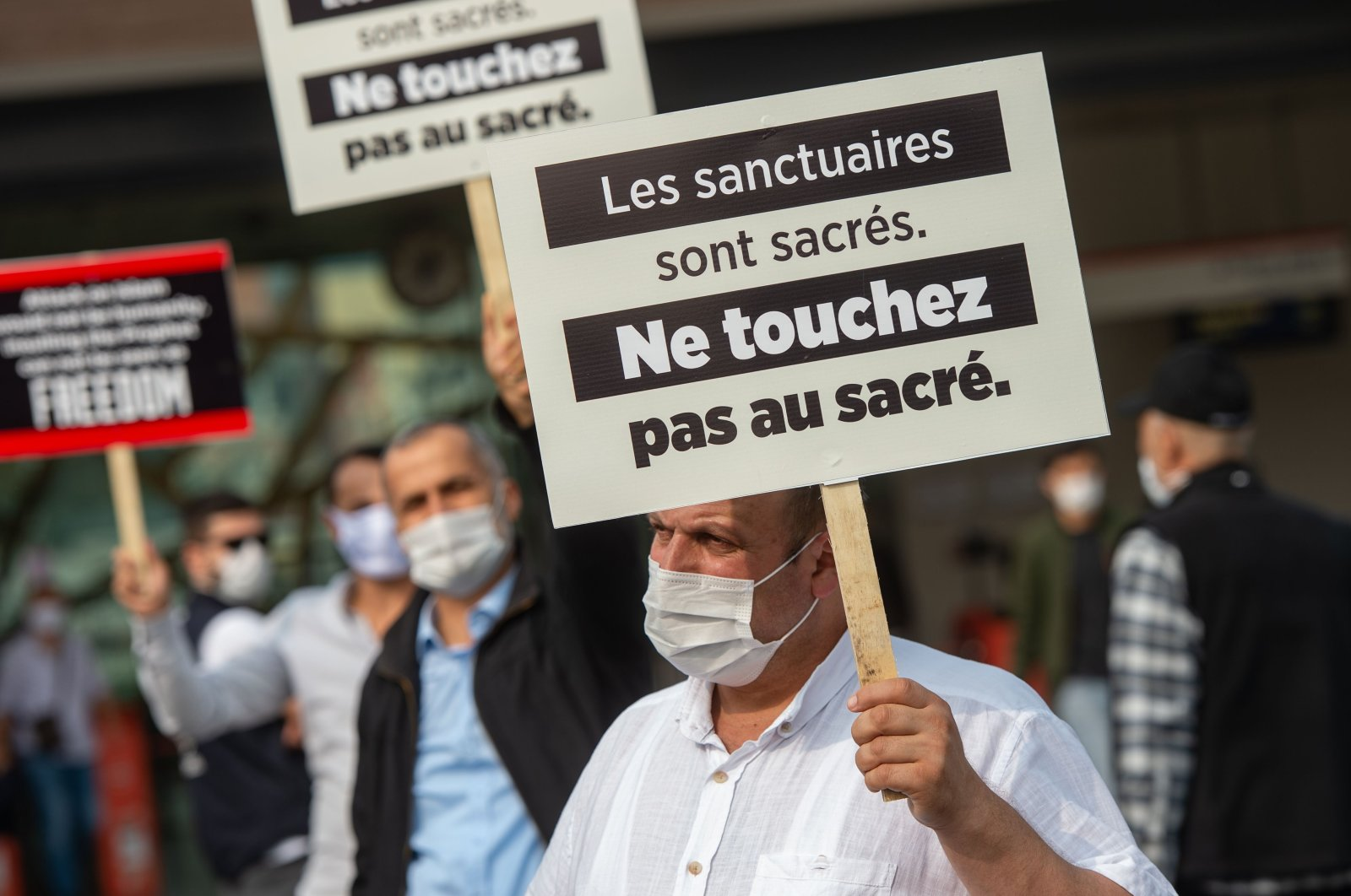 Men hold signs reading ' Places of Worship are Holy. Don't touch the Holy' during a demonstration against French President's comments over Prophet Muhammad cartoons, in Istanbul, on October 27, 2020. (AFP Photo)