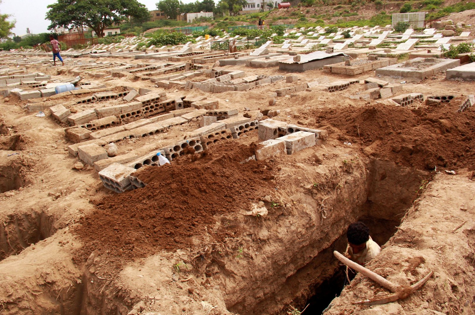 A man digs a grave at a cemetery where victims of the coronavirus disease (COVID-19) are buried in Taiz, Yemen, June 23, 2020. (Reuters Photo)