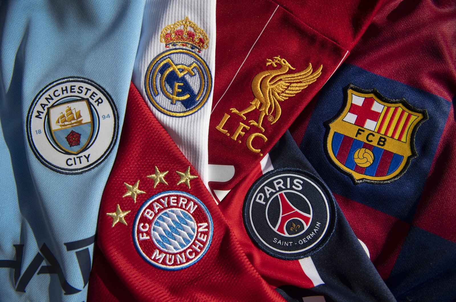 Badges of Manchester City, Bayern Munich, Real Madrid, Liverpool, Paris St-Germain and FC Barcelona on display, in Manchester, Britain, Oct. 20, 2020. (Getty Images)