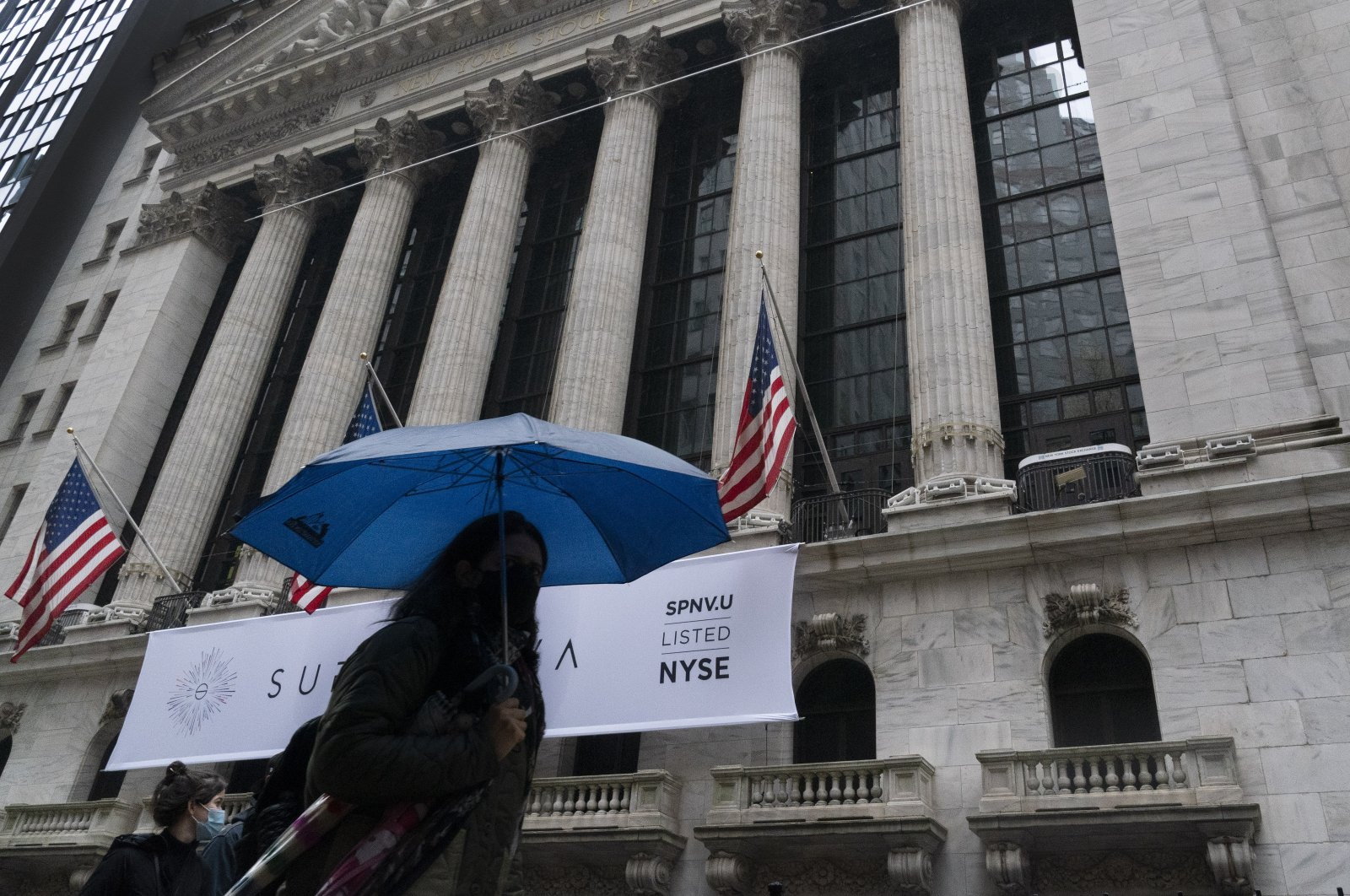 A woman with an umbrella passes the New York Stock Exchange, Monday, Oct. 26, 2020 (AP Photo)