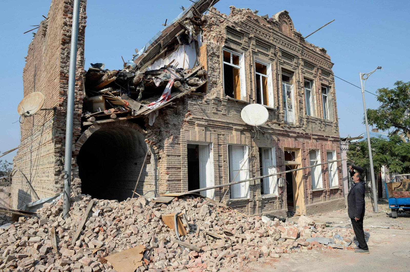 A man looks at a residential building damaged by Armenian shelling, in Ganja, Azerbaijan, Oct. 27, 2020. (AFP Photo)