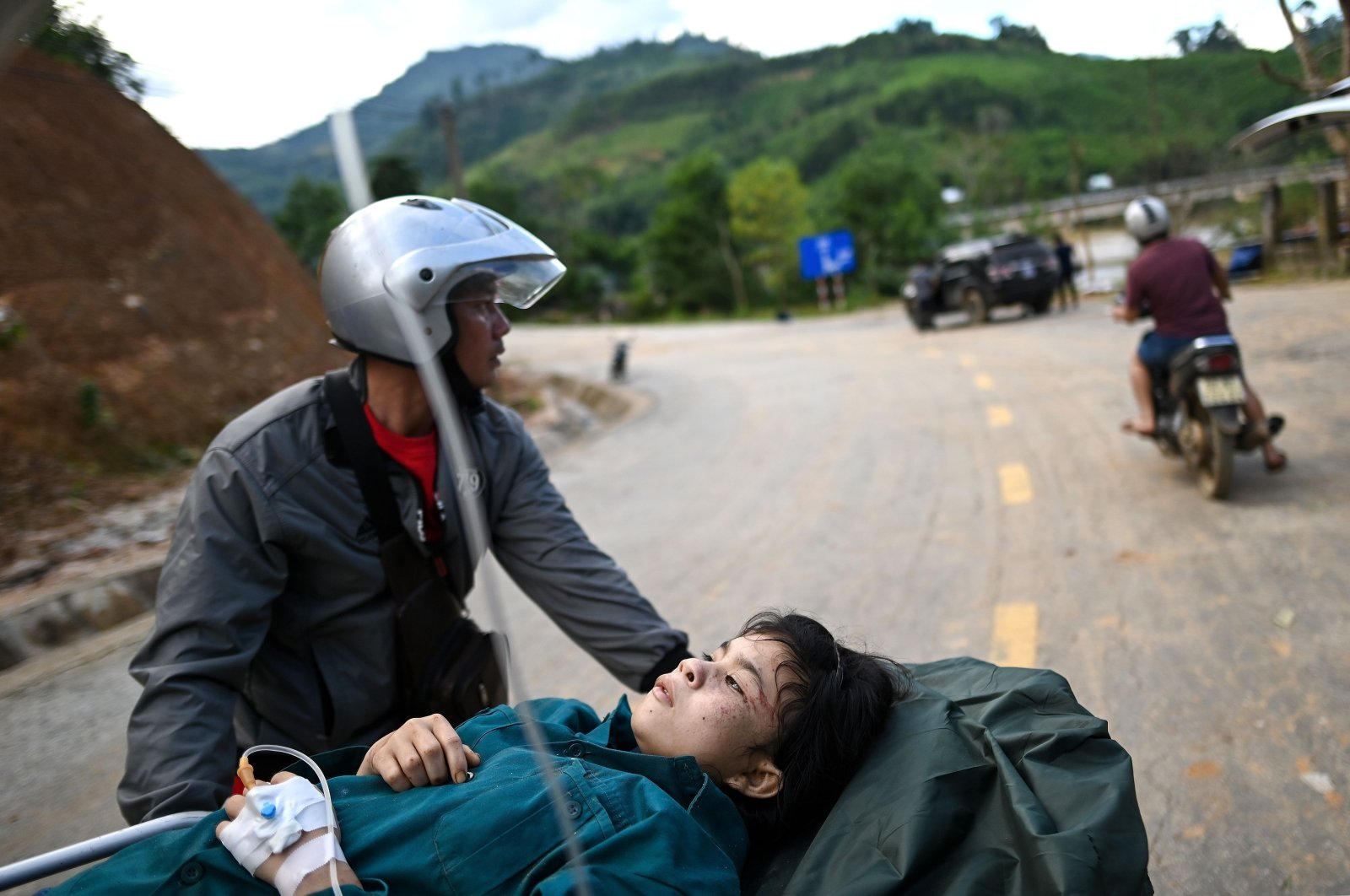 An injured woman is carried on a stretcher to an ambulance after being rescued from a landslide in Tra Leng commune in central Vietnam's Quang Nam province on October 29, 2020, in the aftermath of Typhoon Molave. (AFP Photo)