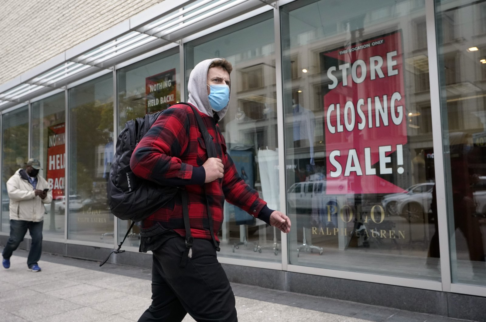 A passerby walks past a store closing sign in the window of a department store, in Boston, U.S., Oct. 27, 2020. (AP Photo)