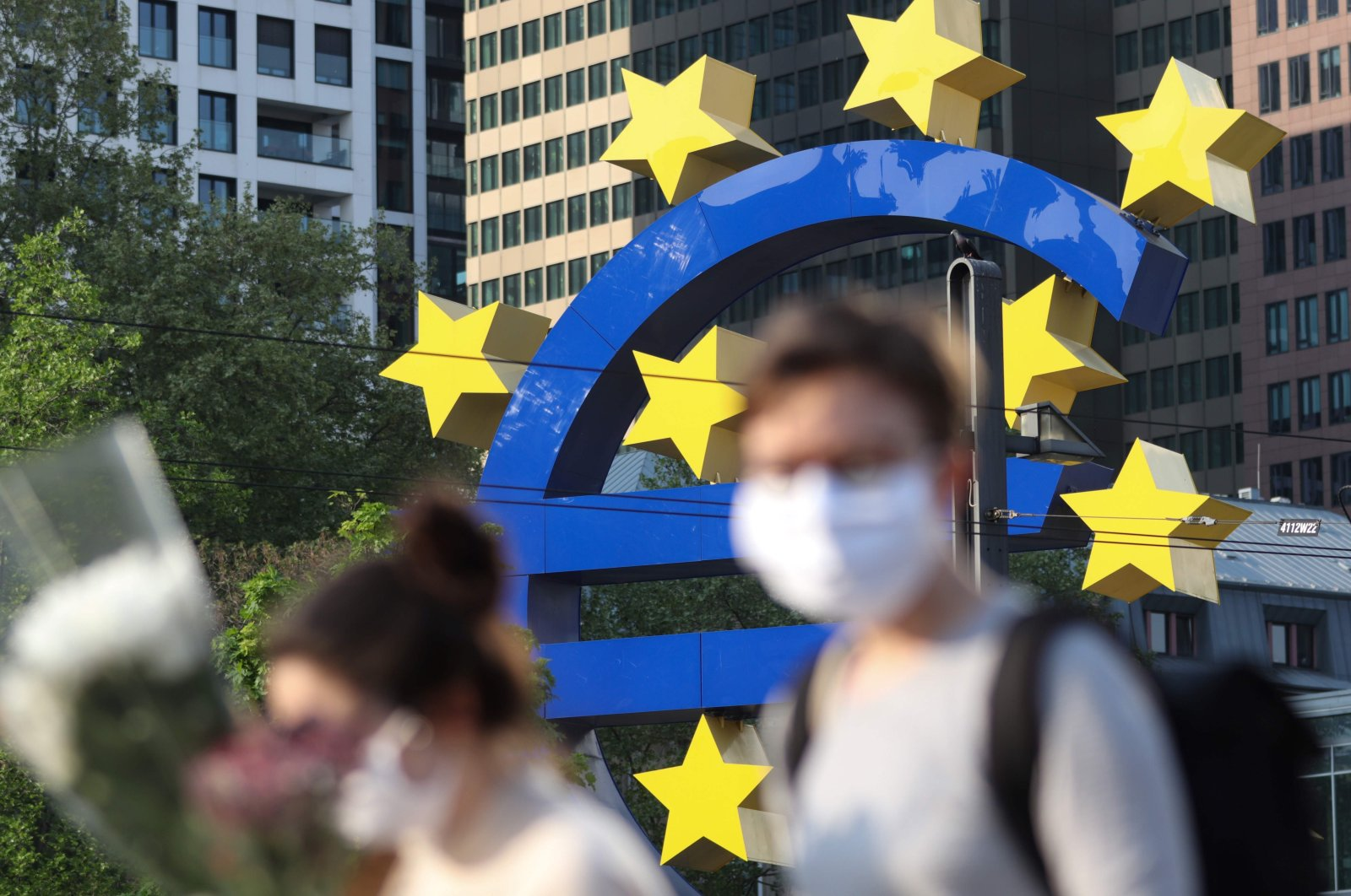 People wearing face masks walk in front of a big euro sign as the European Central Bank (ECB) headquarter can be seen in the background, in Frankfurt am Main, western Germany, April 24, 2020. (AFP Photo)