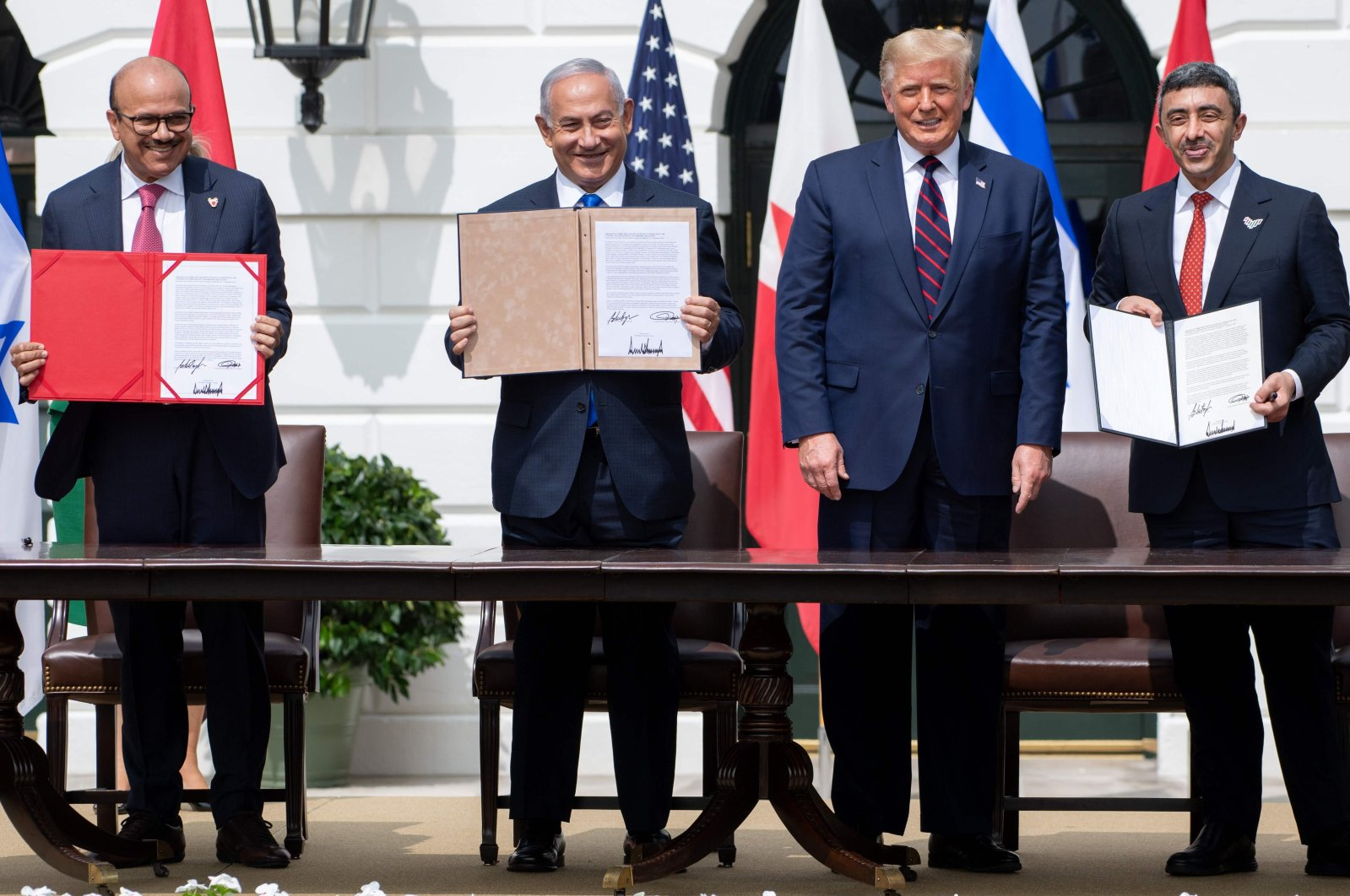 (L-R) Bahrain Foreign Minister Abdullatif al-Zayani, Israeli Prime Minister Benjamin Netanyahu, U.S. President Donald Trump, and UAE Foreign Minister Abdullah bin Zayed Al-Nahyan hold up documents after participating in the signing of the Abraham Accords where the countries of Bahrain and the United Arab Emirates recognize Israel, at the White House in Washington, DC, Sept.15, 2020. (AFP Photo)