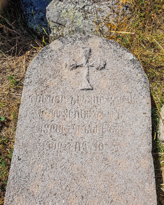 Une pierre tombale dans l'ancien cimetière arménien avec des inscriptions et une croix dessus.  (Photo par Argun Konuk)