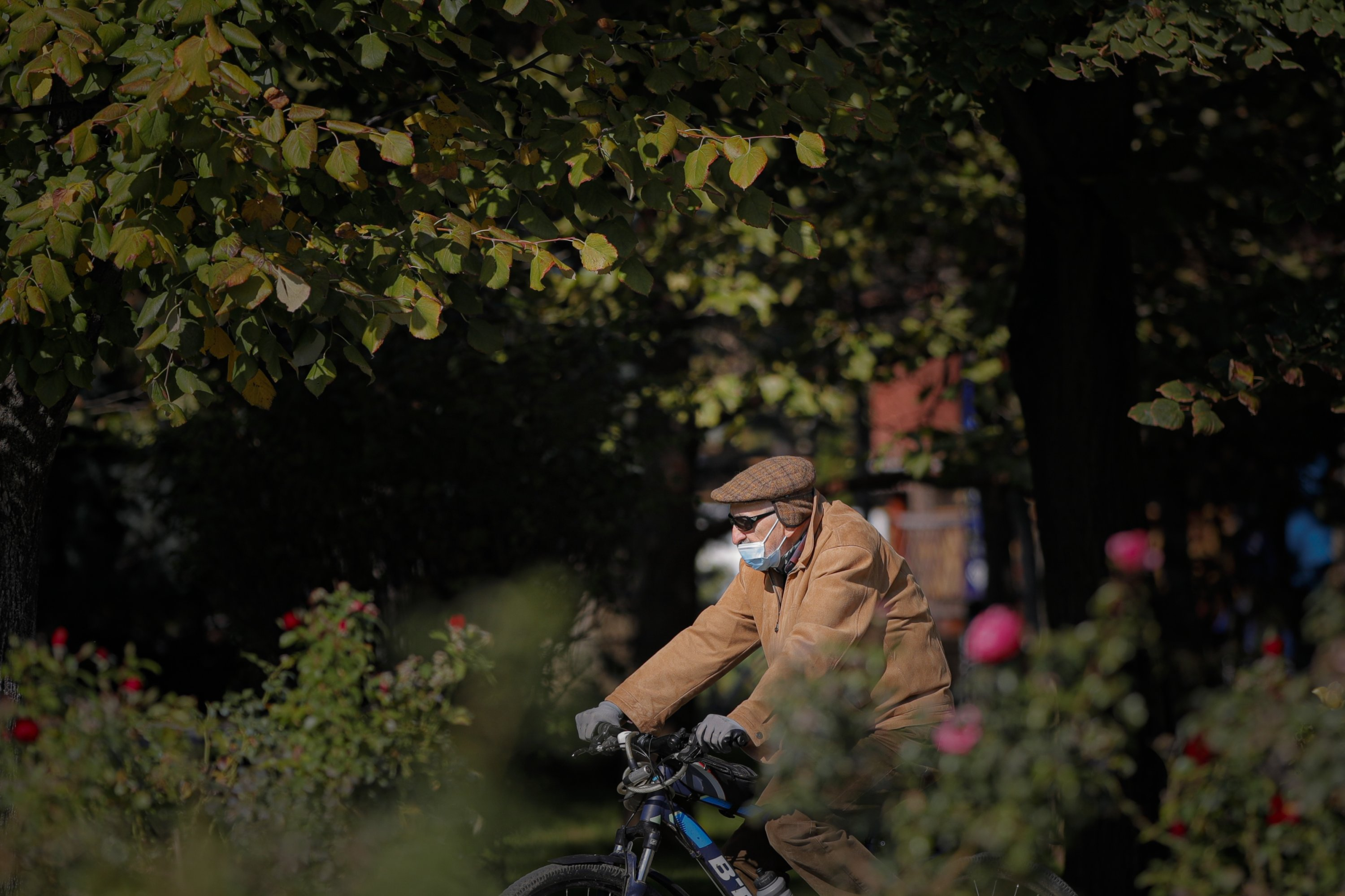 A man wearing a face mask for protection against COVID-19 infection rides a bicycle in Bucharest, Romania, Oct. 20, 2020. (AP Photo)