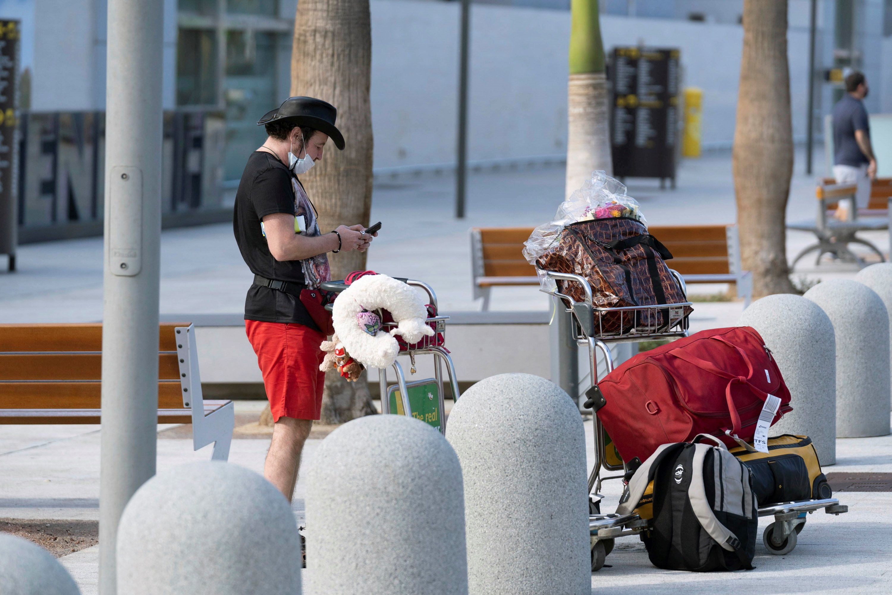 A tourist checks his cellphone next to his luggage after arriving, outside Tenerife Sur international airport in Tenerife, Canary Islands, Spain, Oct. 24, 2020. (EPA Photo)