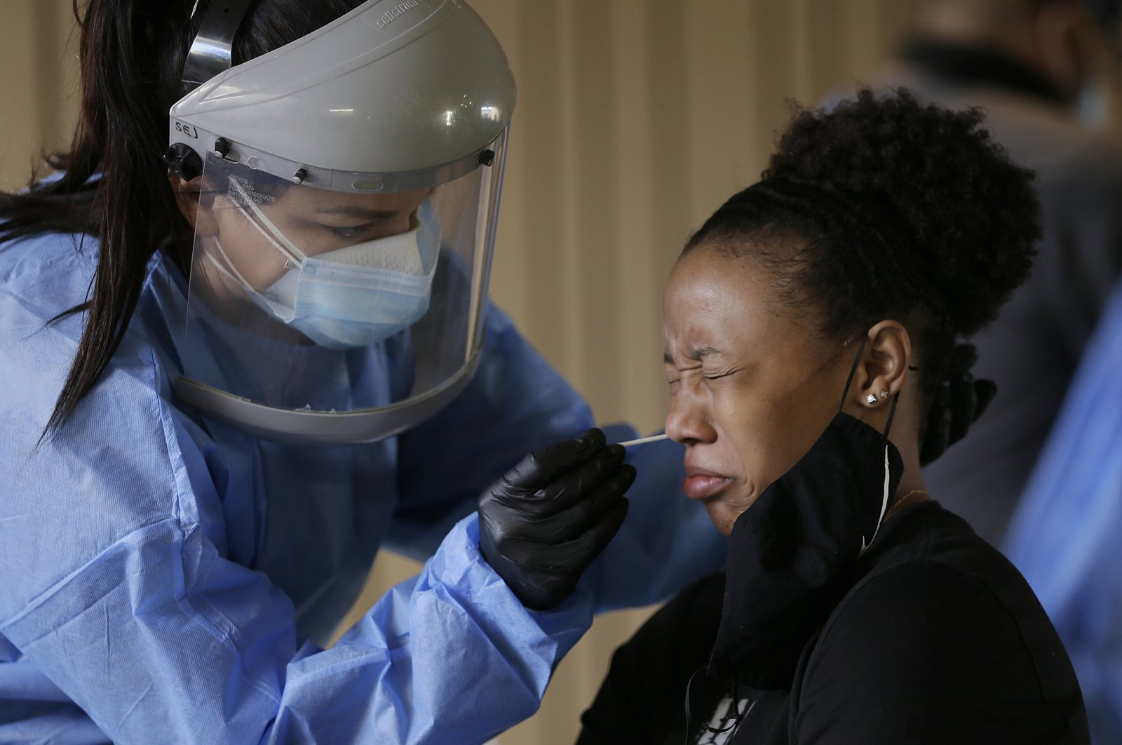 A medical worker tests a university student for coronavirus at the UTEP Fox Fine Arts Center in El Paso, Texas, U.S., Oct. 16, 2020. (The El Paso Times via AP)