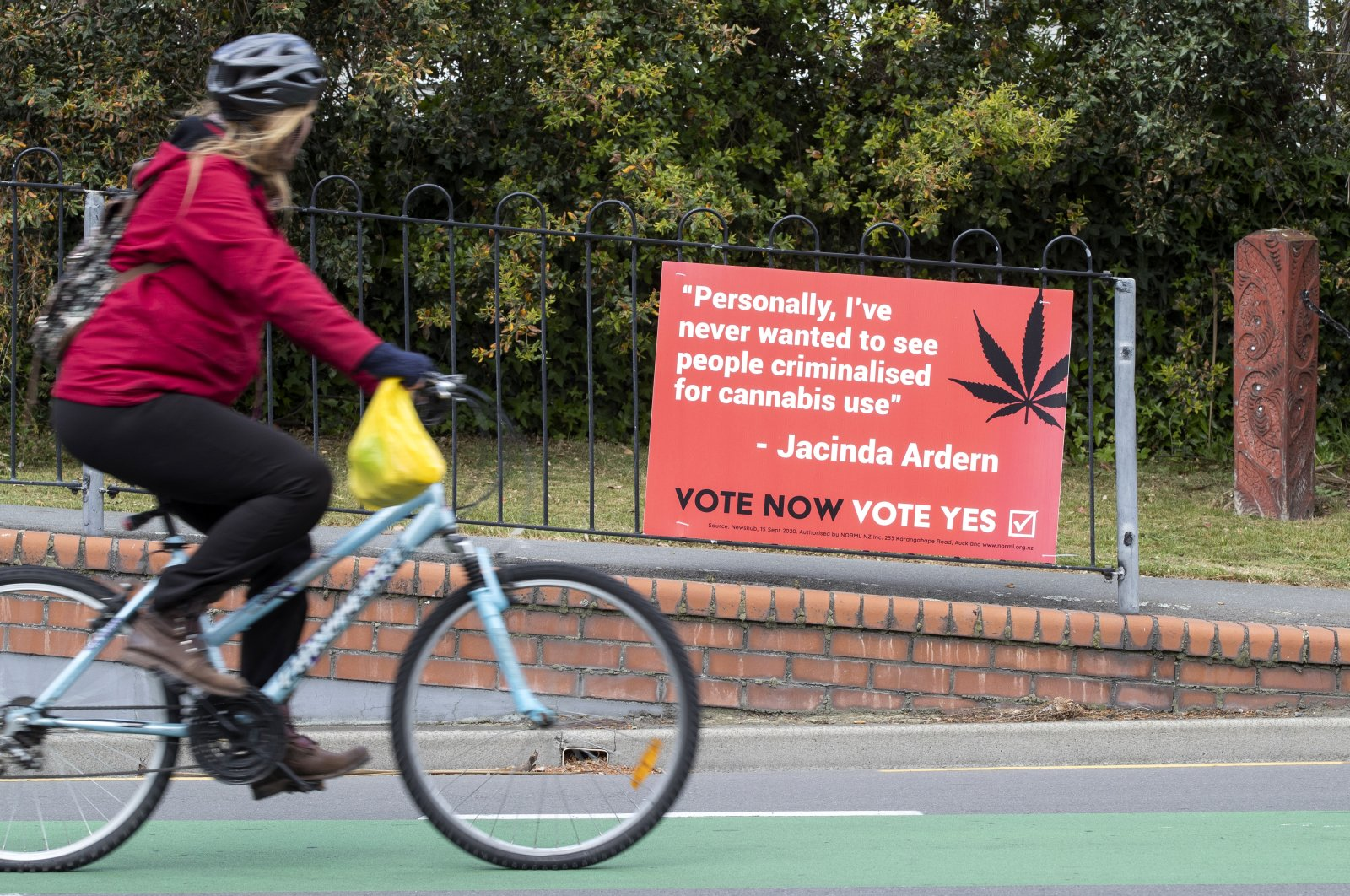In this Oct. 15, 2020, file photo, a cyclist rides past a sign in support of making marijuana legal in Christchurch, New Zealand. (AP Photo)