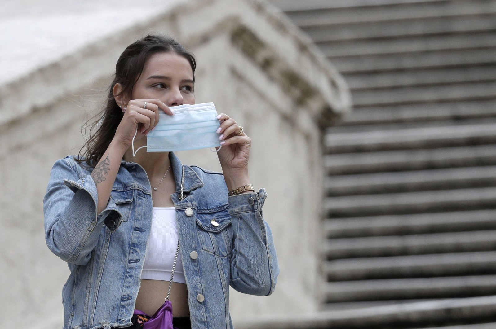 A woman puts on a face mask as a precaution against infection during the coronavirus pandemic, in Rome, Italy, Oct. 6, 2020. (AP Photo)
