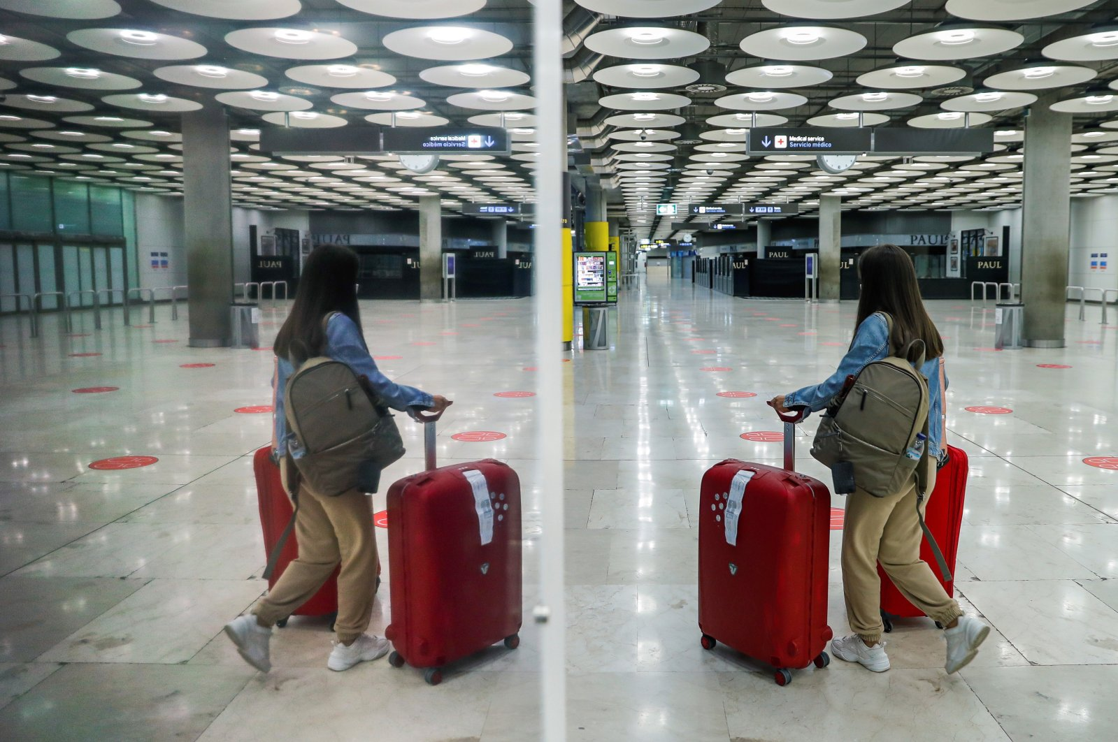 A traveler (R) and her reflection are seen at Adolfo Suarez-Madrid Barajas Airport, Spain, Oct. 2 2020. (EPA Photo)