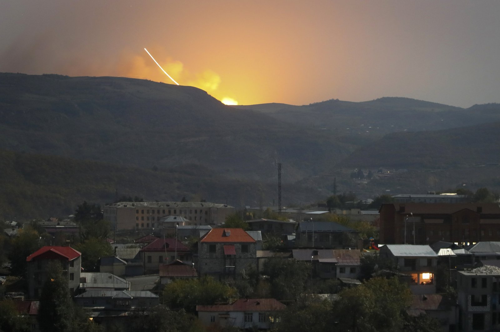Explosions are seen behind the mountains during a military conflict outside Stepanakert (Khankendi) in the Armenian-occupied region of Nagorno-Karabakh, Oct. 30, 2020. (AP Photo)