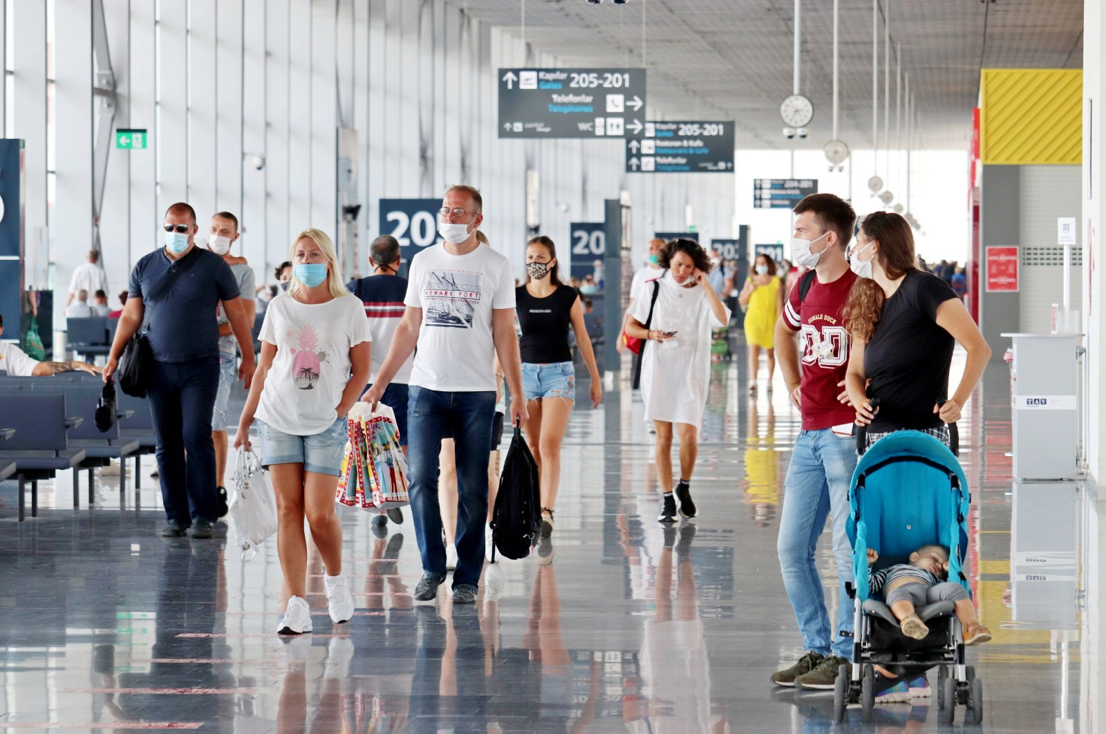 Tourists in masks walk in a terminal at Bodrum-Milas Airport during the coronavirus pandemic, southern Muğla province, Turkey. (Shutterstock photo by Oleg Elkov)